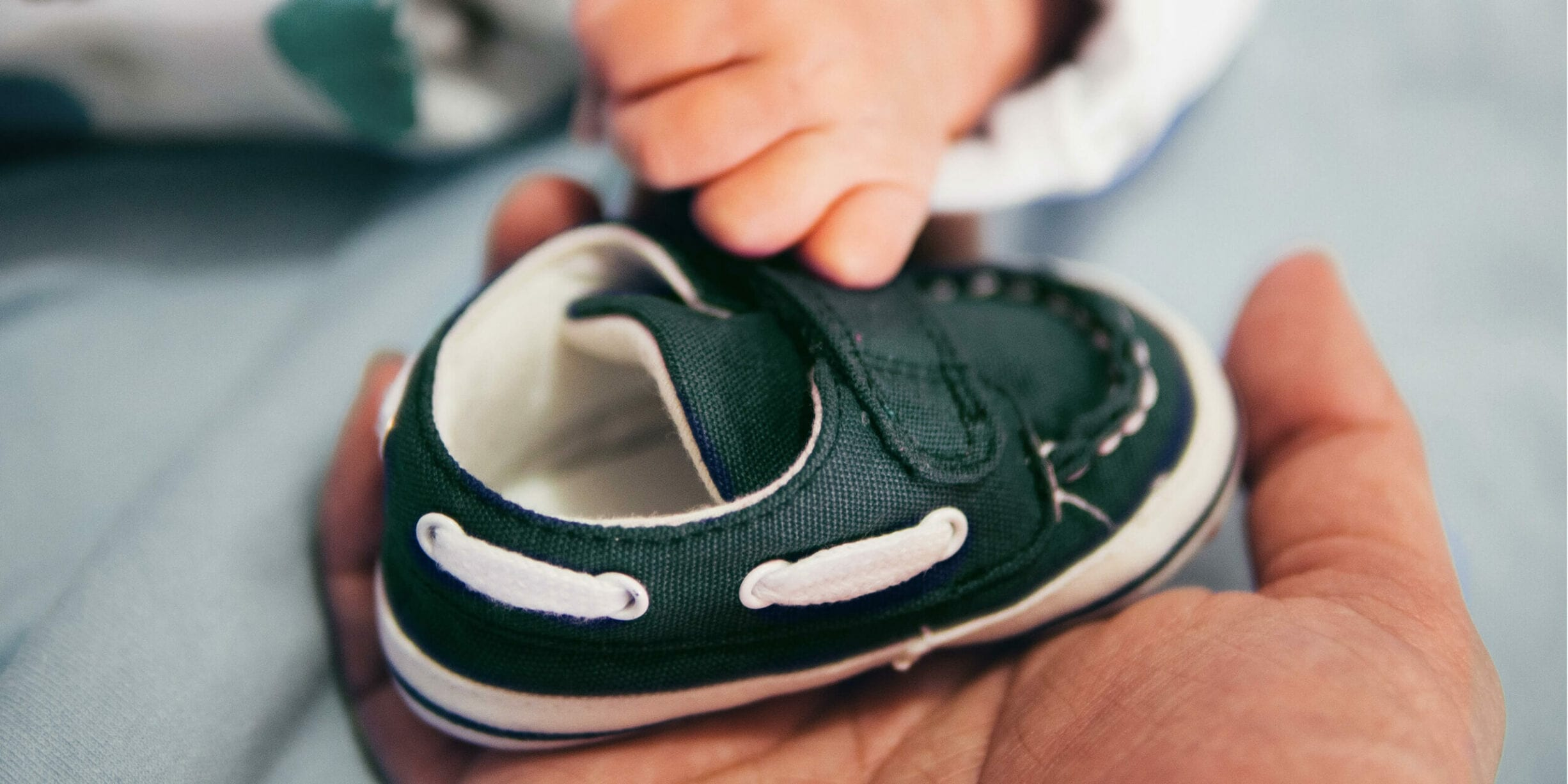 parent holding child shoe, baby hand