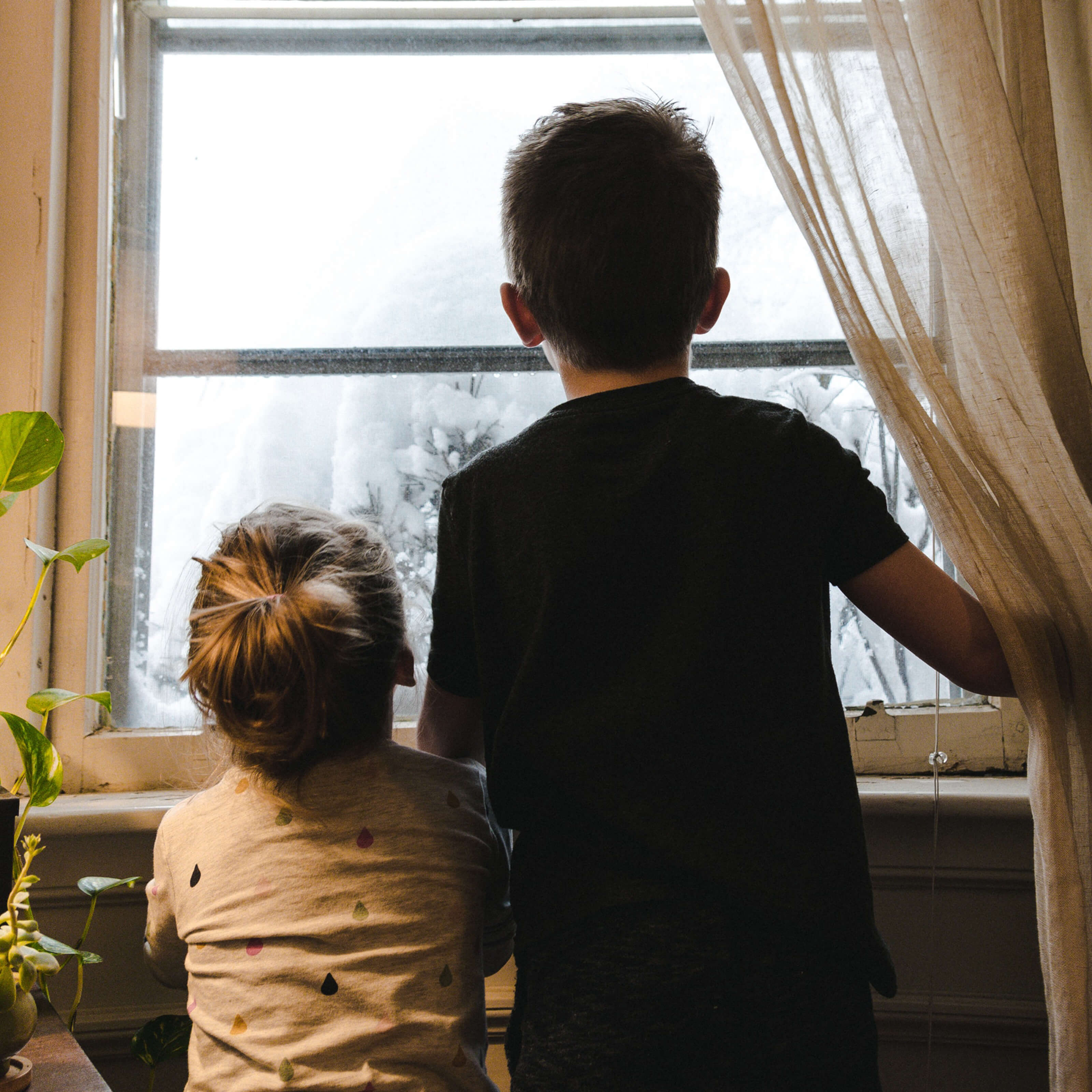 two boys staring out window