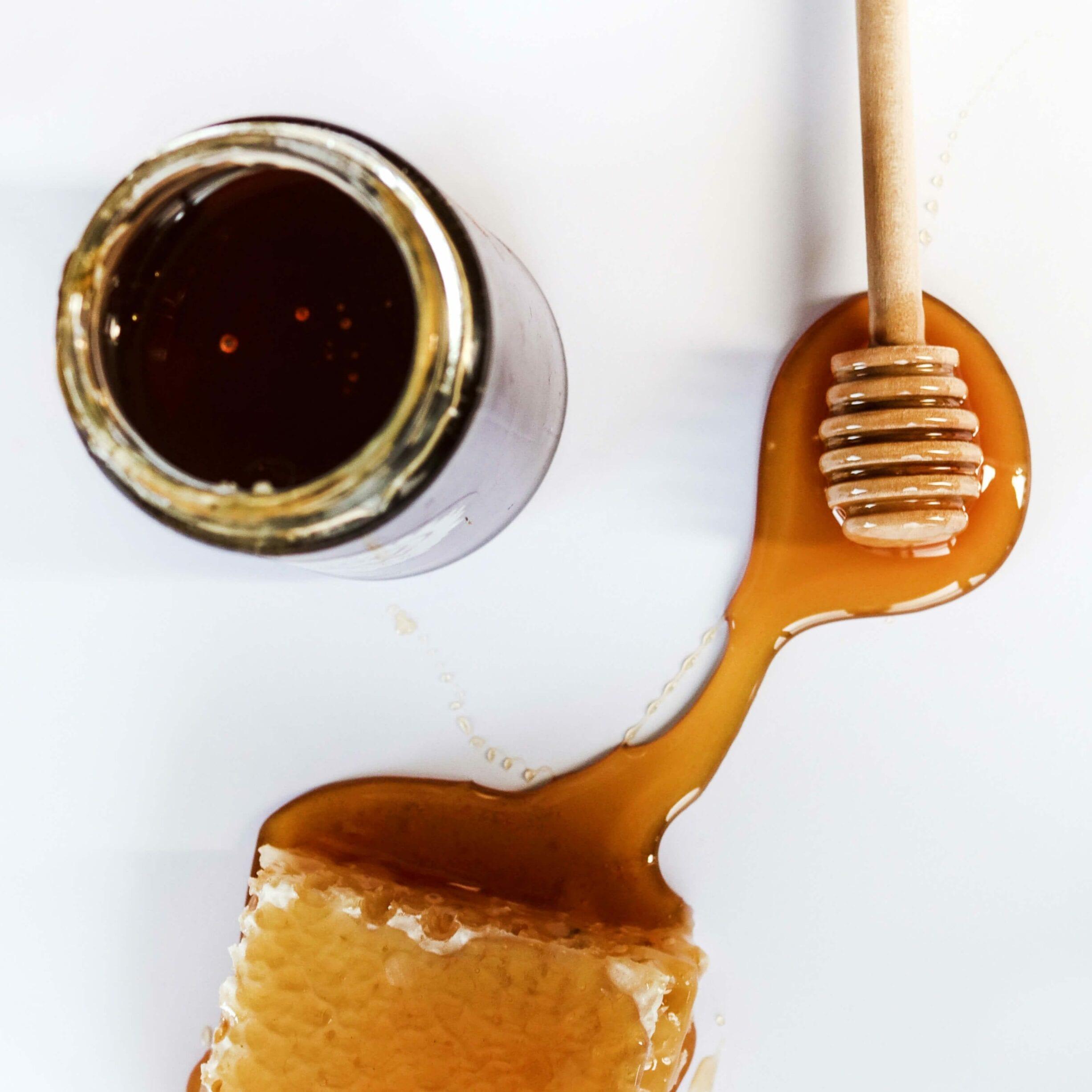 jar of honey, stirrer, piece of honeycomb
