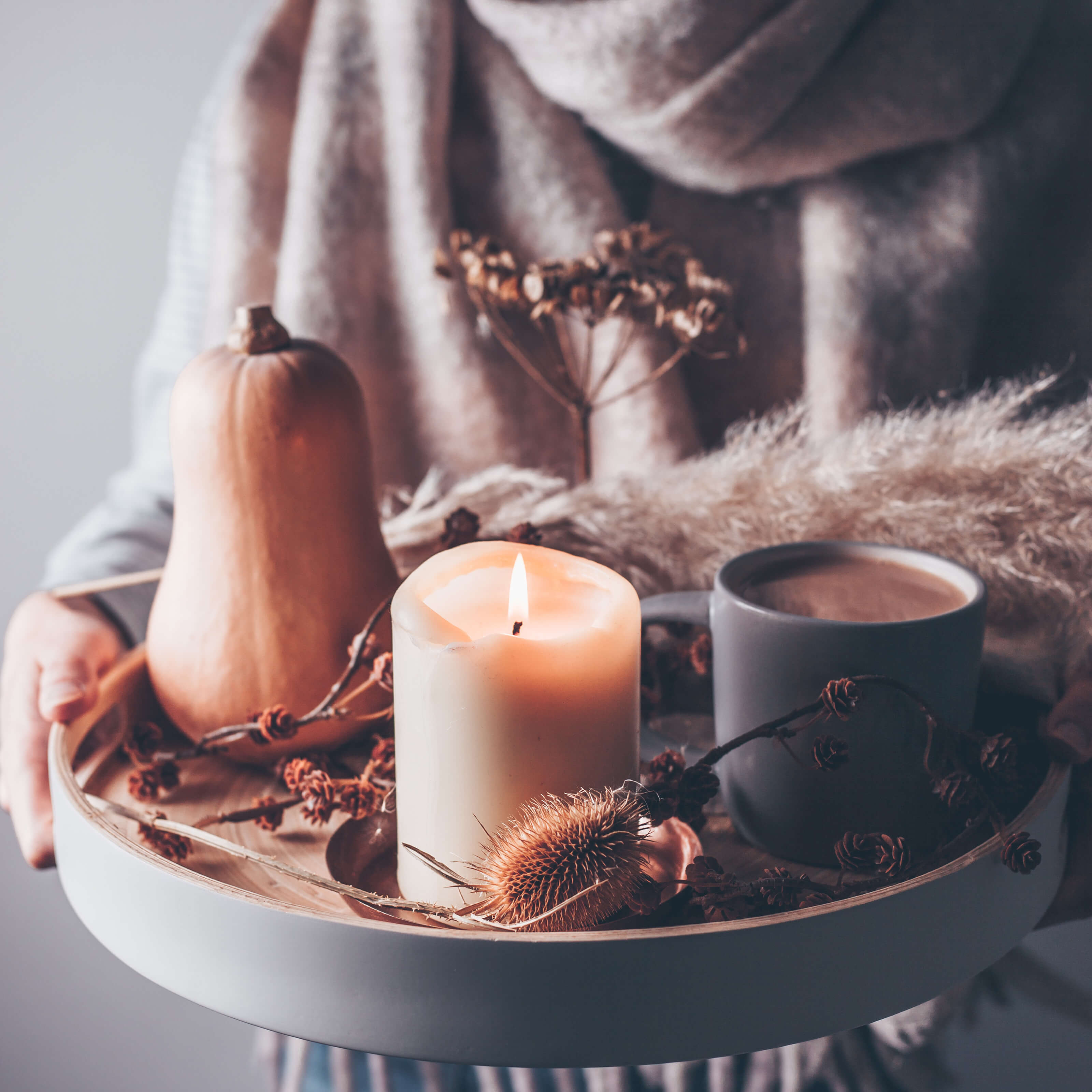 woman holding tray with lit candle, mug of hot chocolate, squash