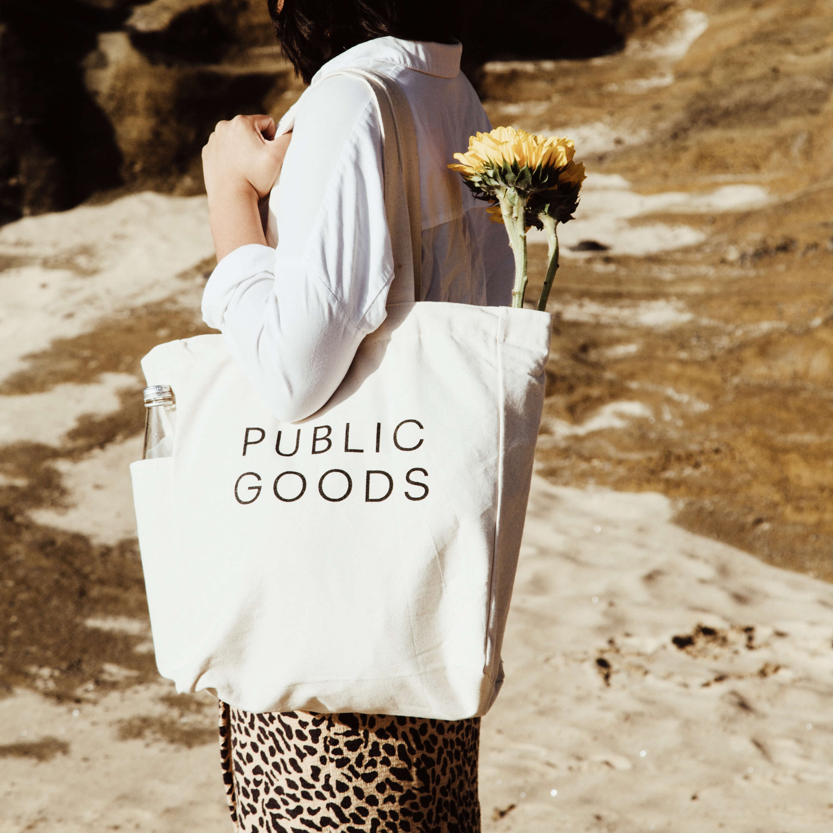 woman holding public goods tote bag with flowers