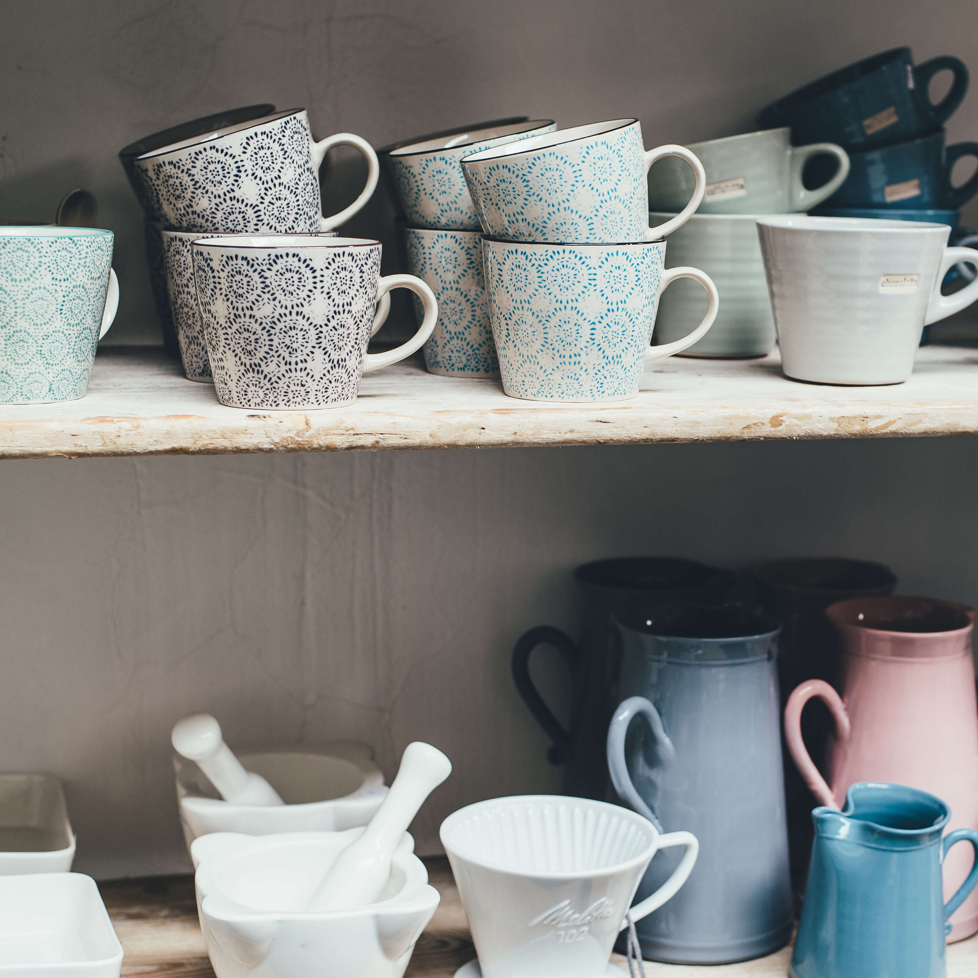 stacked tea cups and pitchers on shelves, mortar and pestle