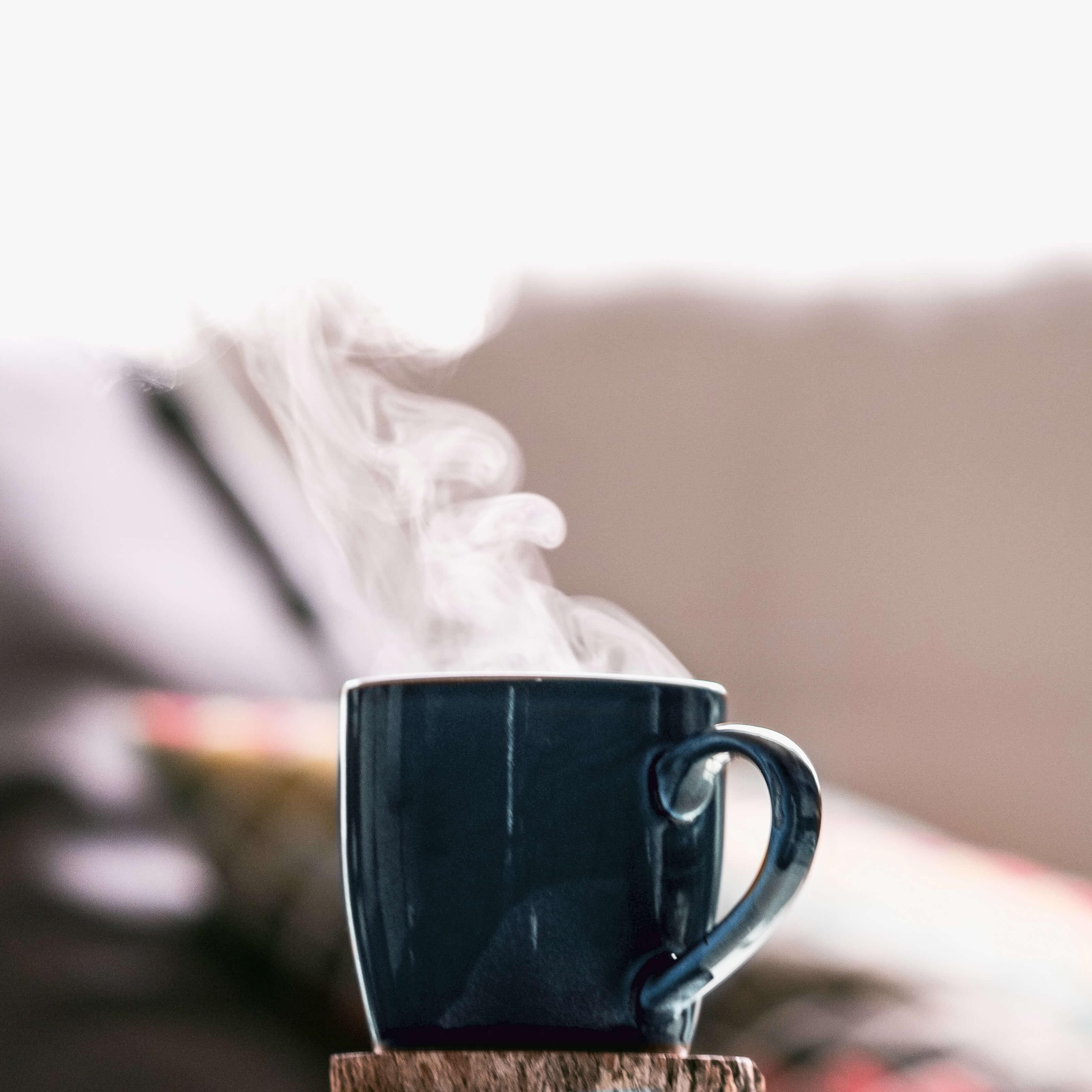 blue mug on wooden coaster, steam rising