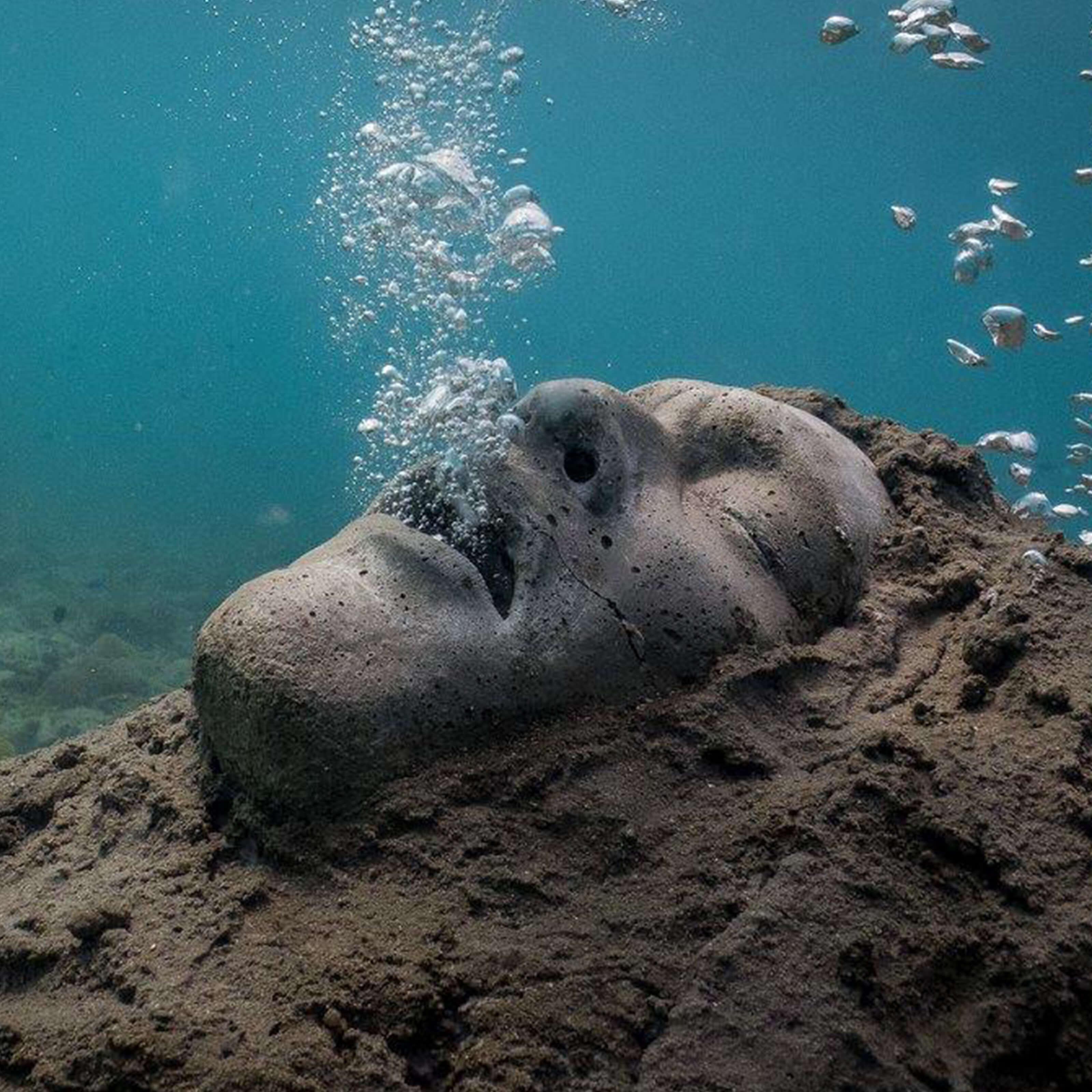 underwater face sculpture, hand