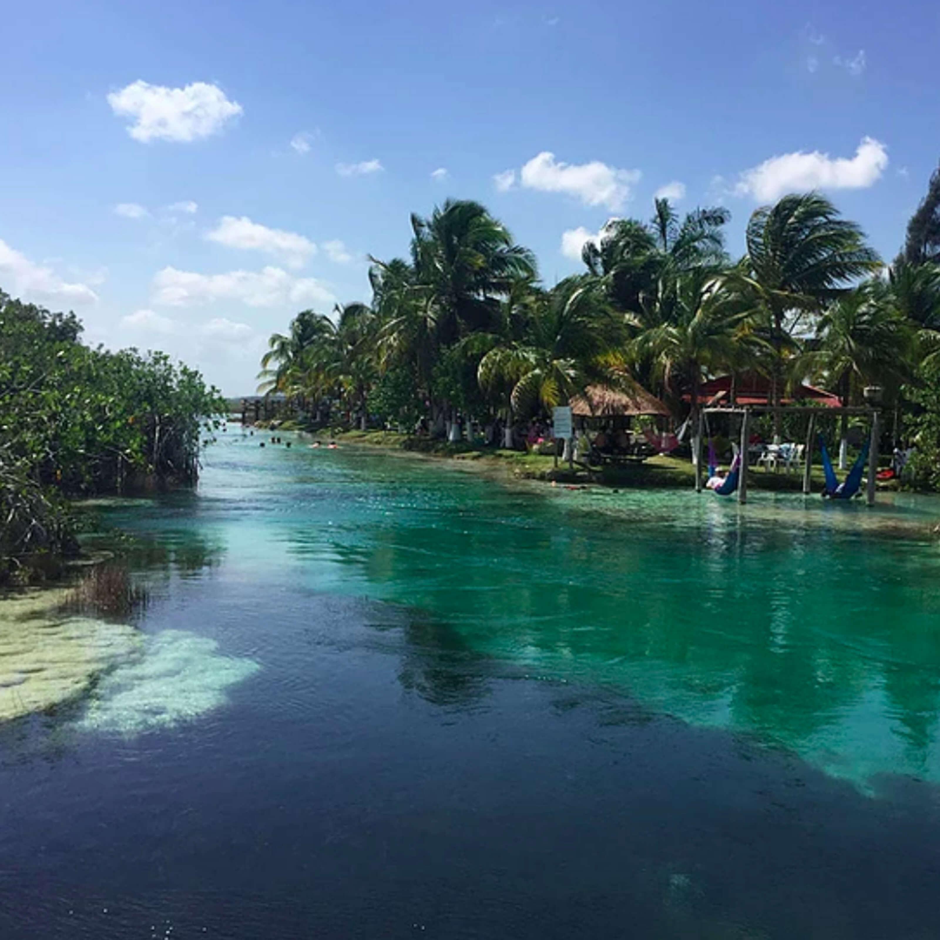 lagoon, trees, huts, hammocks, swimmers