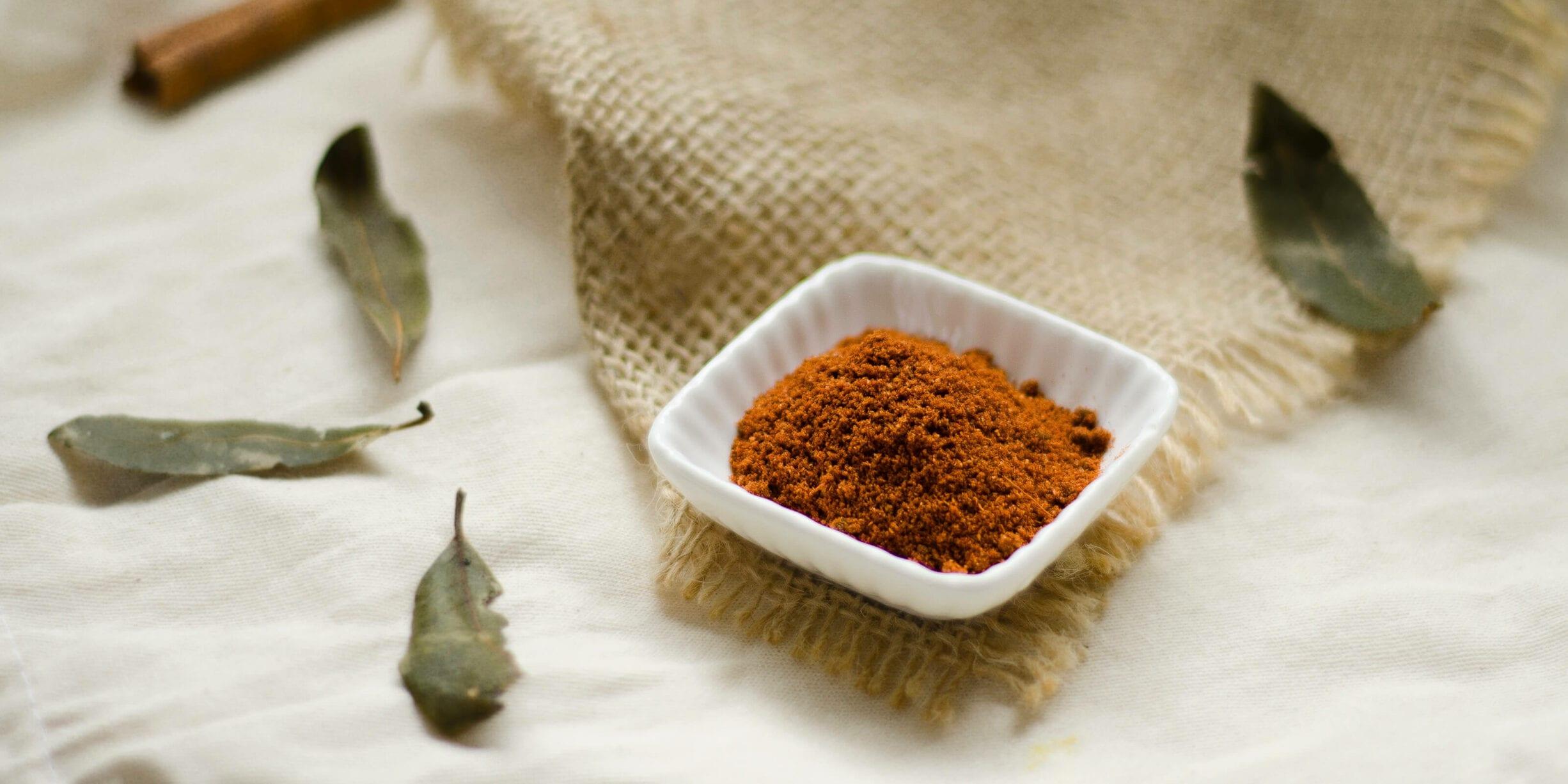 cinnamon powder in bowl, leaves, cloth
