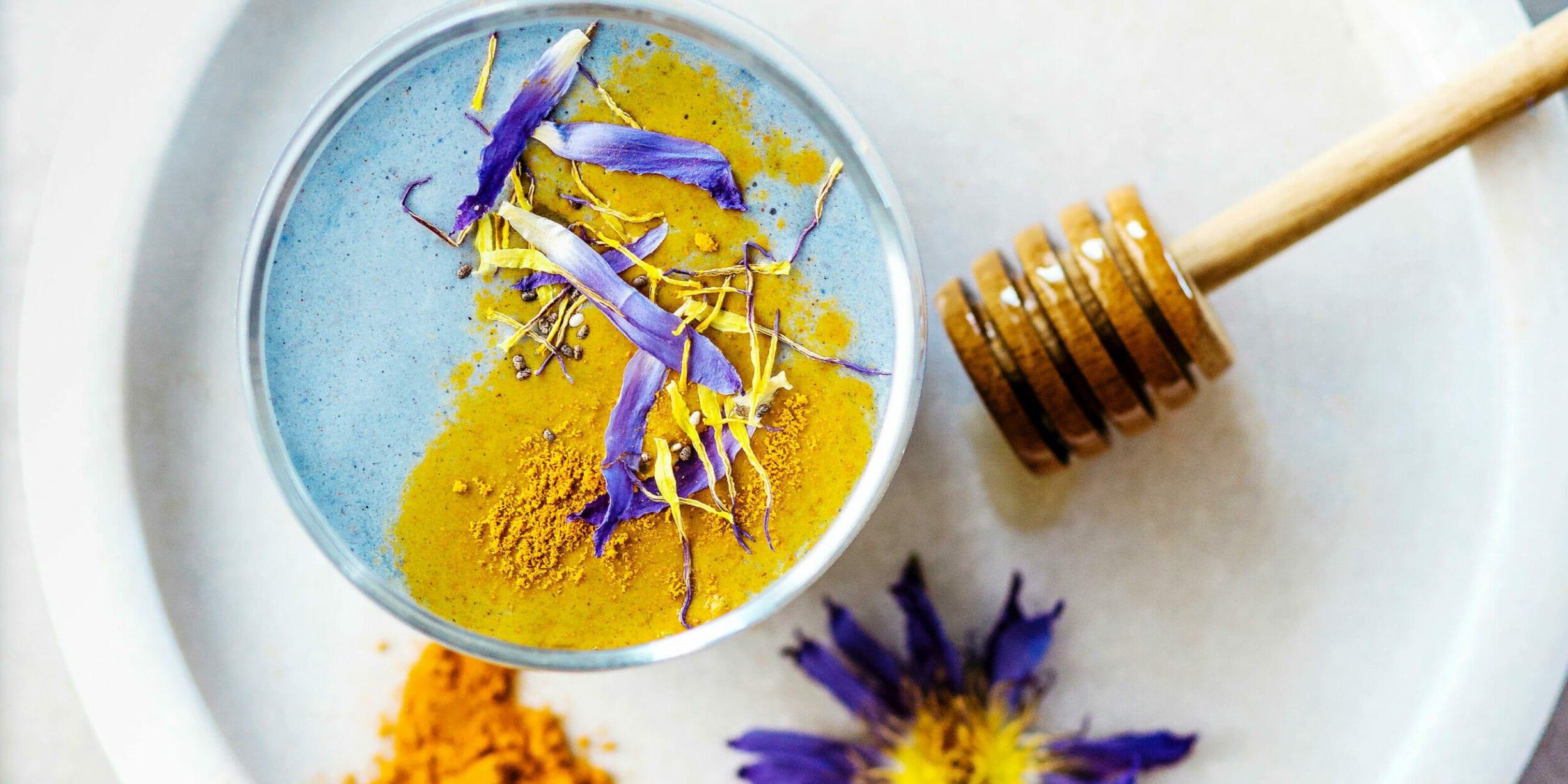bowl of tumeric, honey dropper, flowers