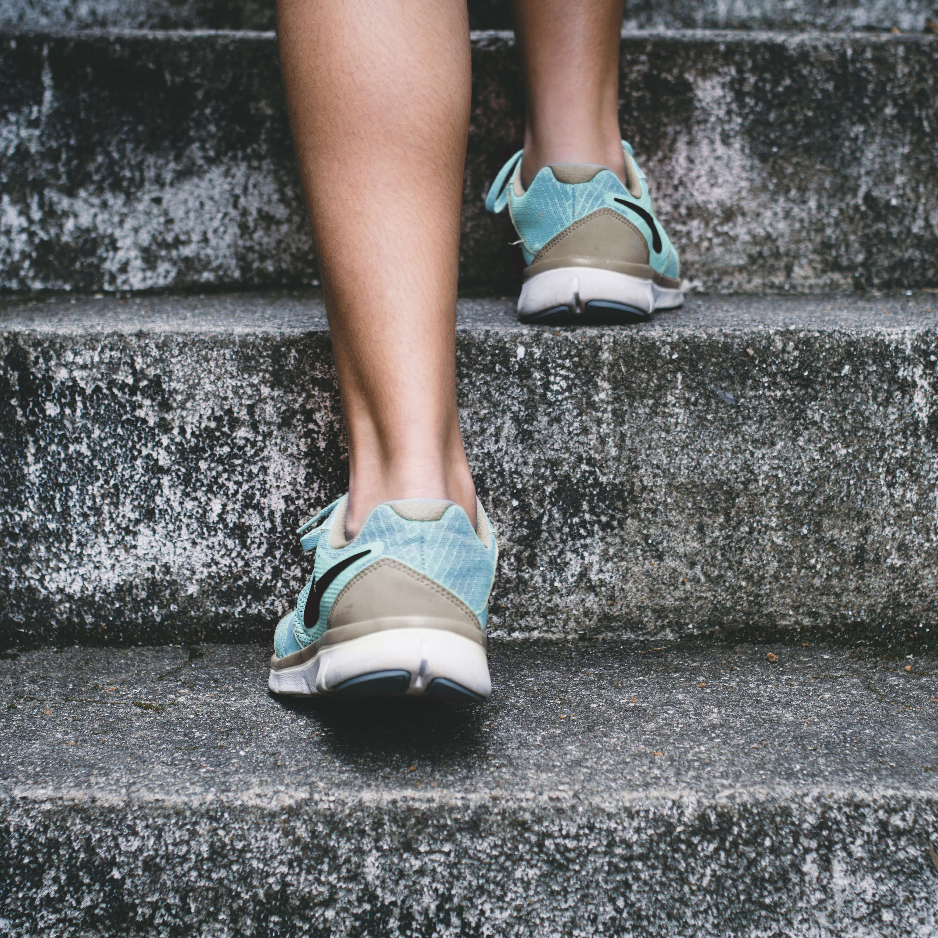 legs jogging up stairs, running shoes