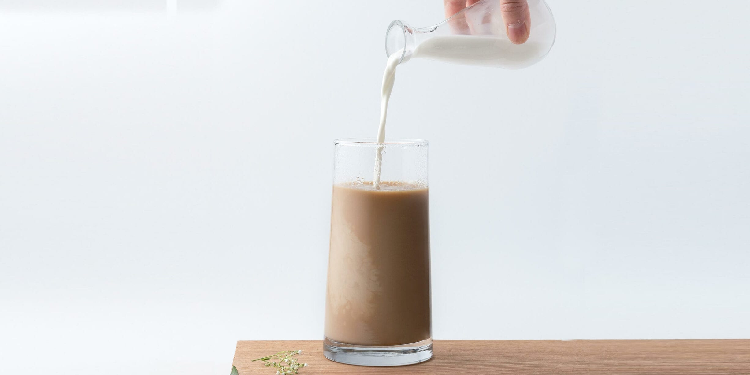 milk being poured into tall glass of coffee