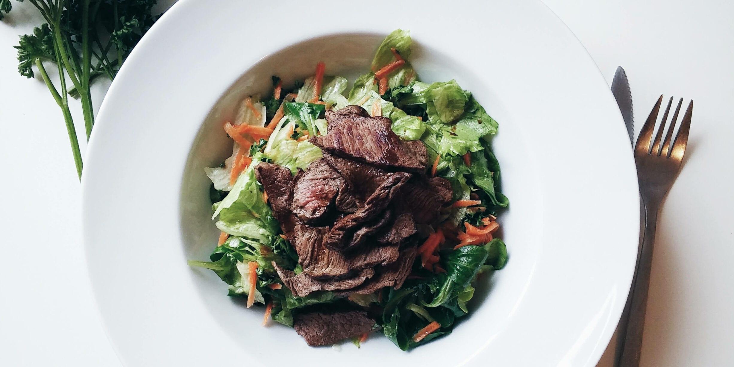 beef salad in bowl, fork