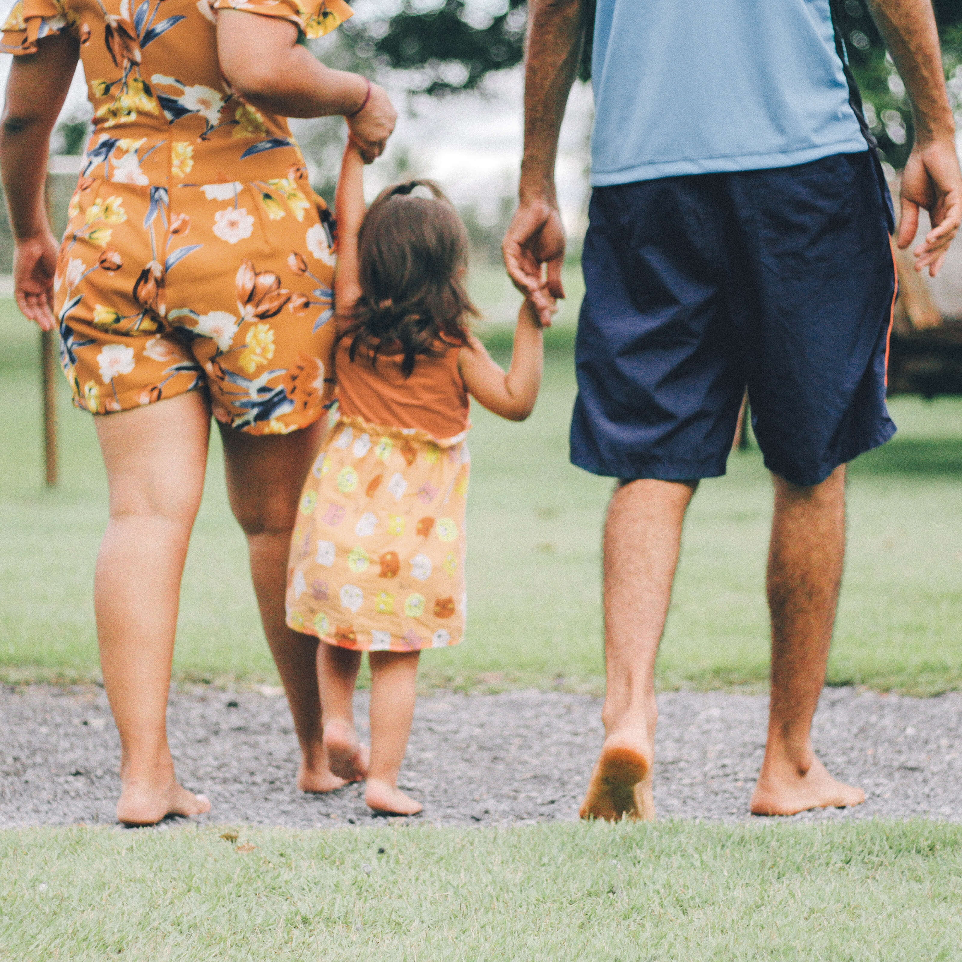 mother and father holding hands with young daughter