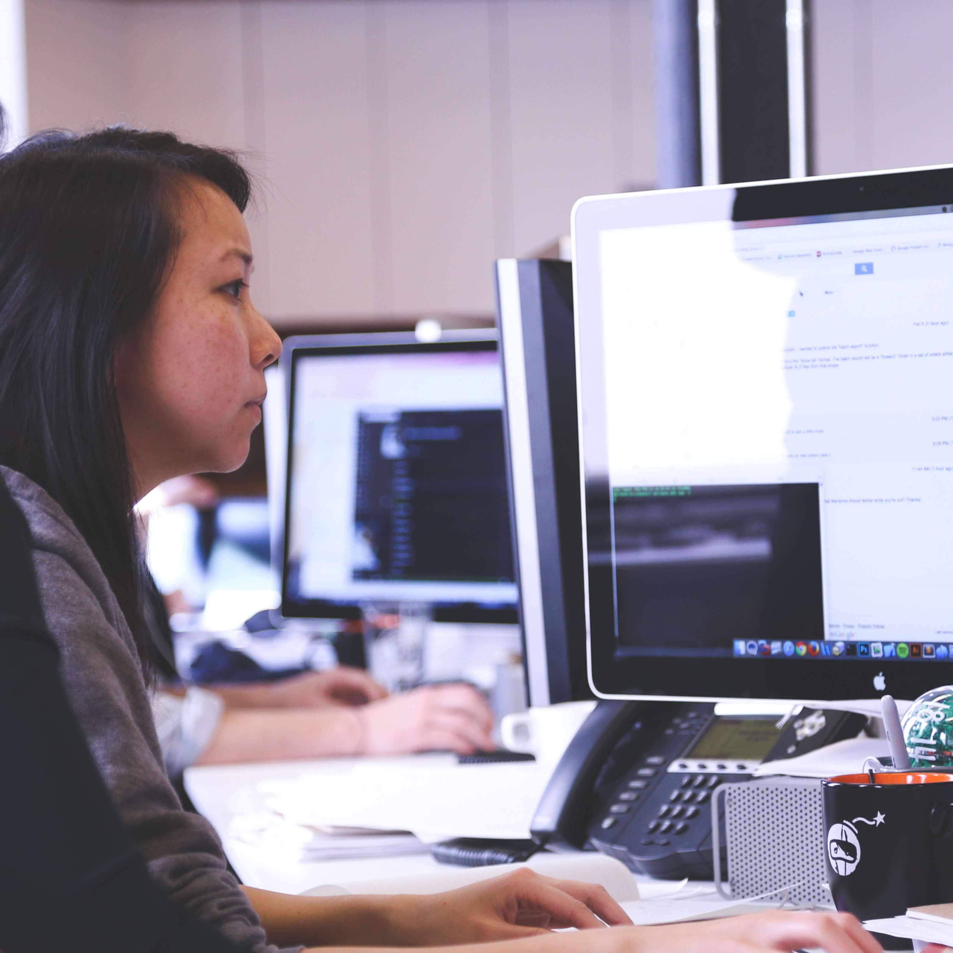 asian woman typing at desk, computer monitors