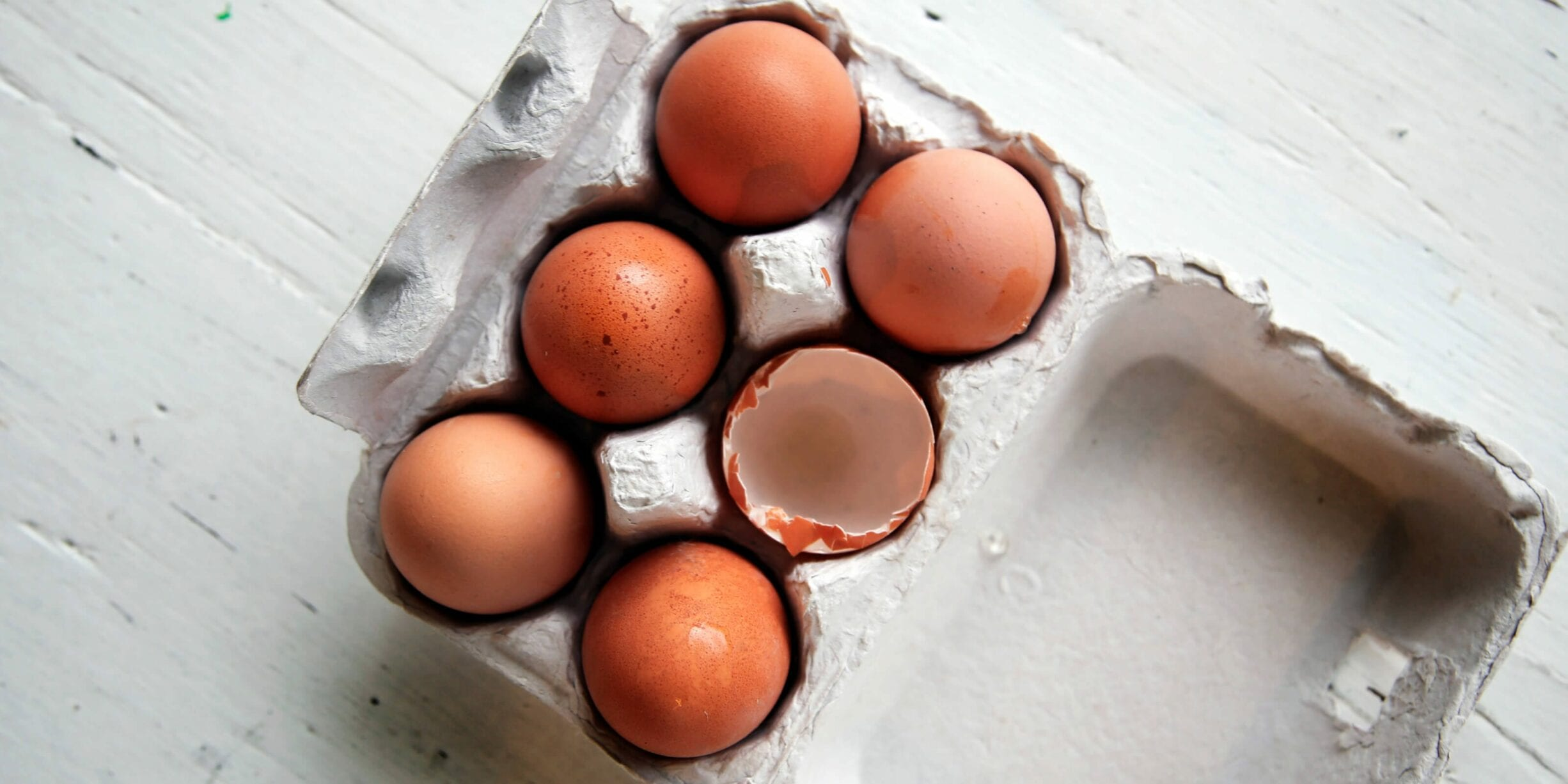 carton of six brown eggs, one cracked