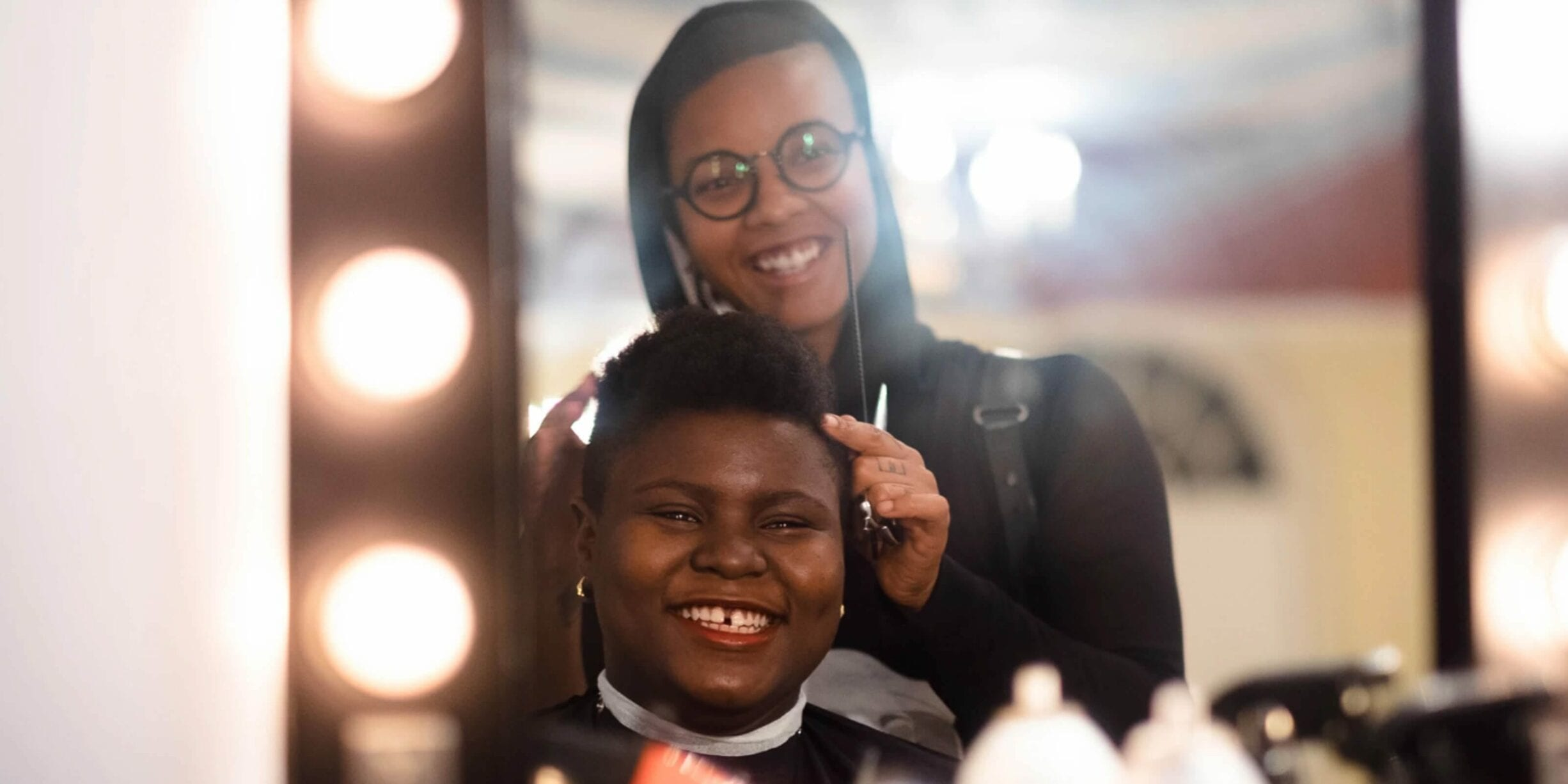 madin lopez giving haircut to young black LGBTQ person