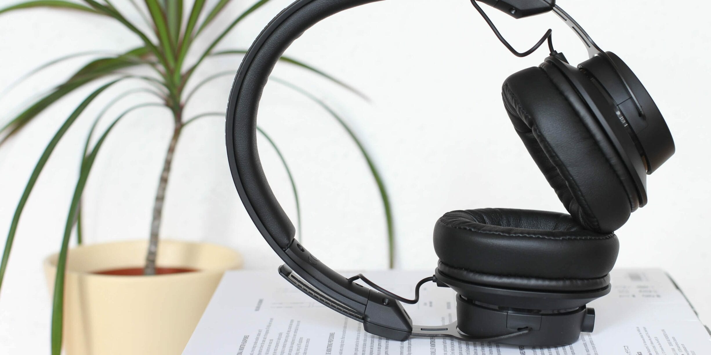black headphones, paper, house plant
