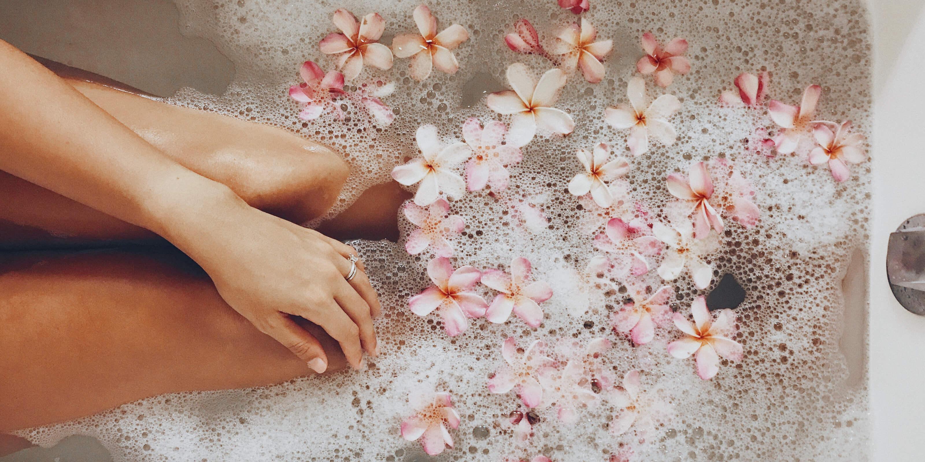 bath tub, flower petals, soap bubbles, woman's hand and legs