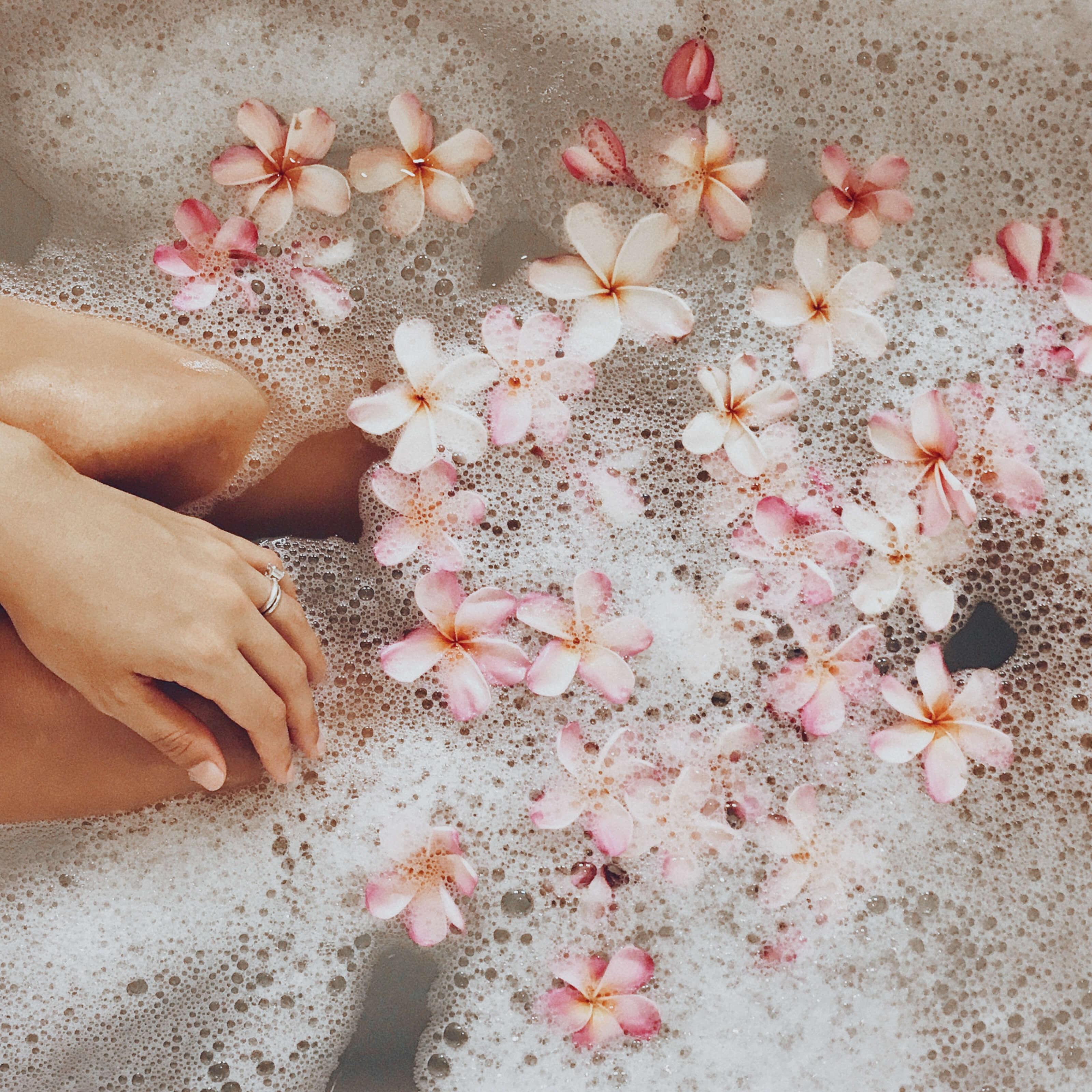 bath tub, flower petals, soap bubbles, woman's hand and legs