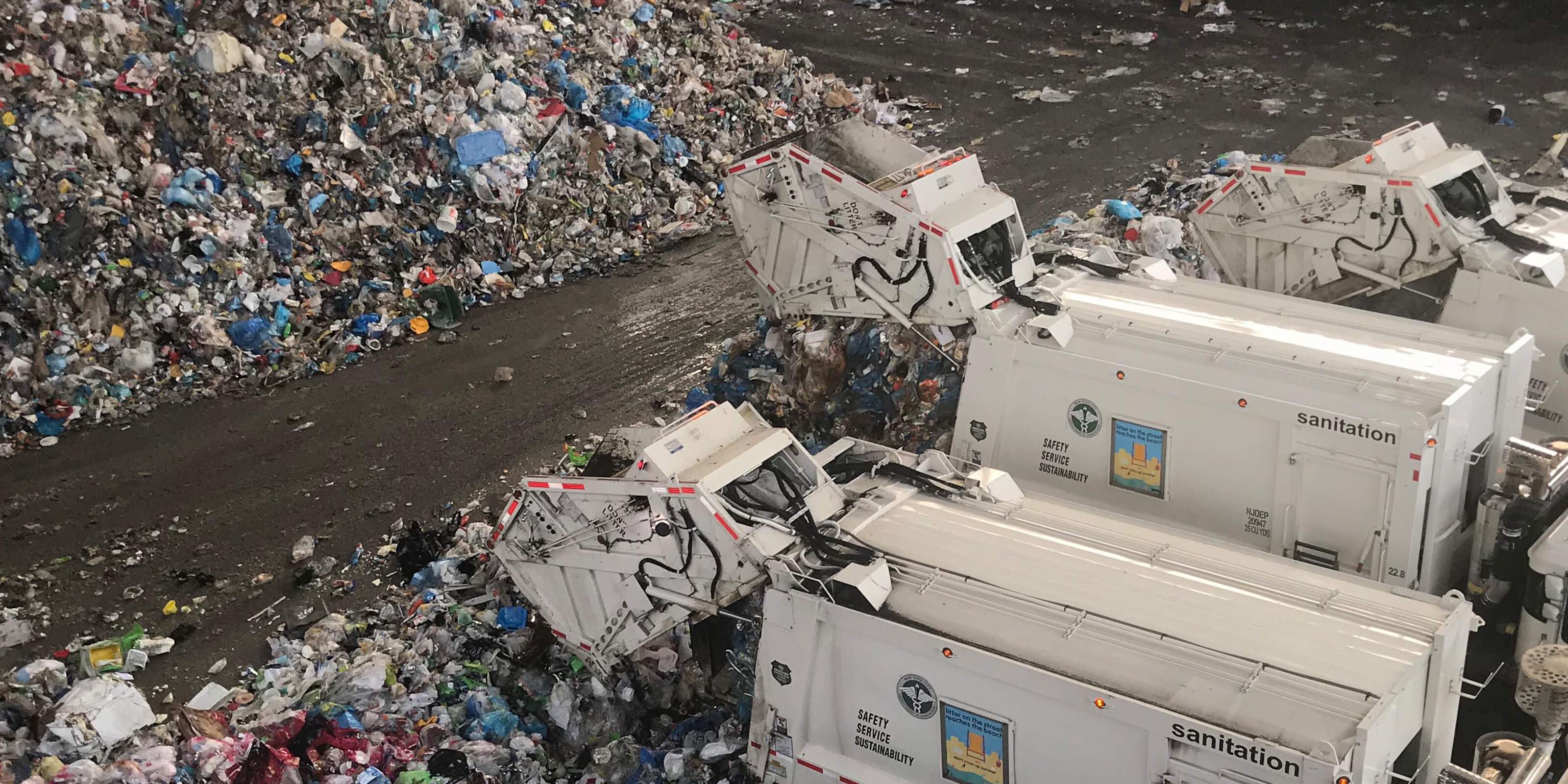 trucks dumping recyclable material in warehouse