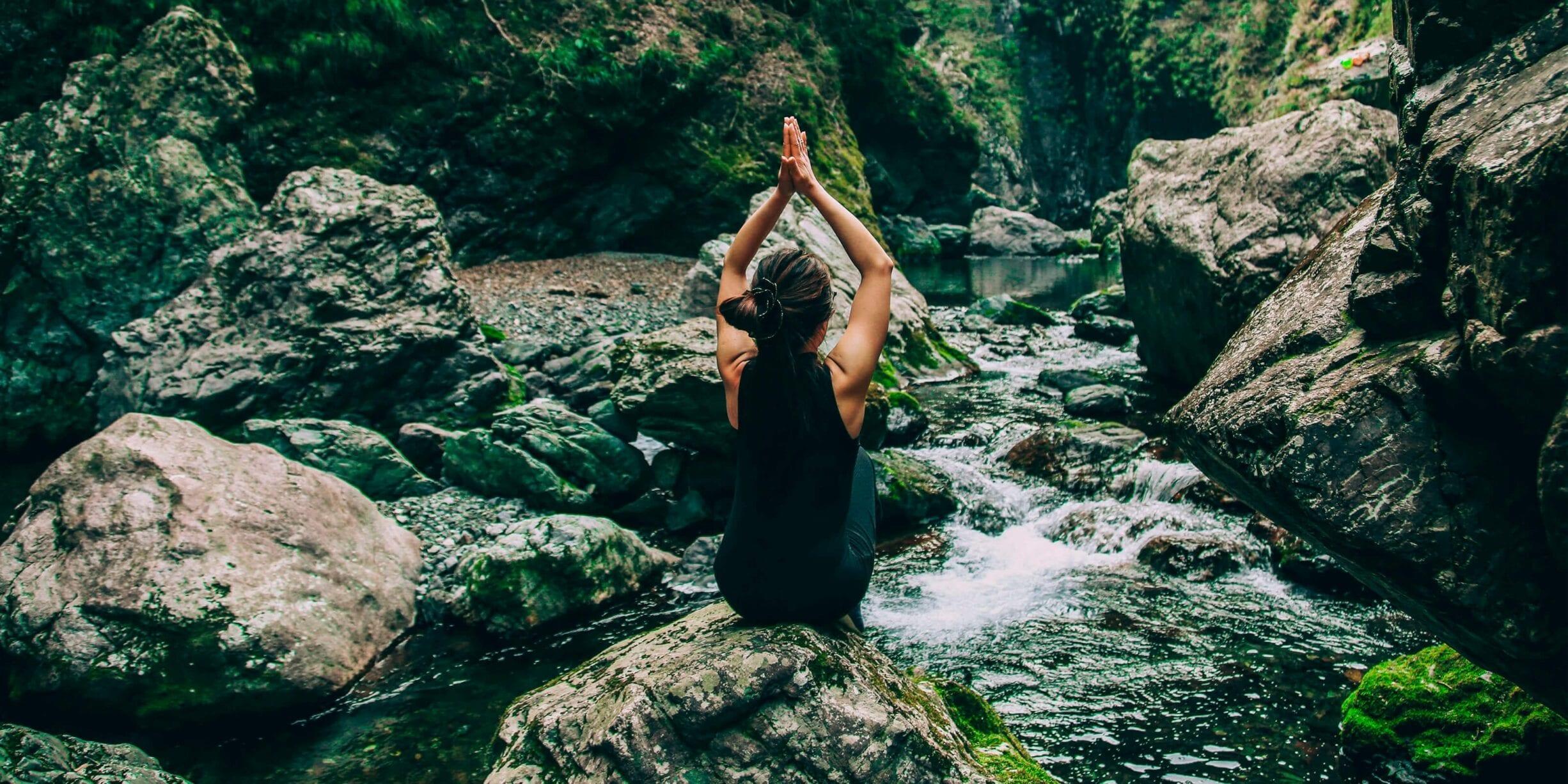 woman meditating sitting on river rocks