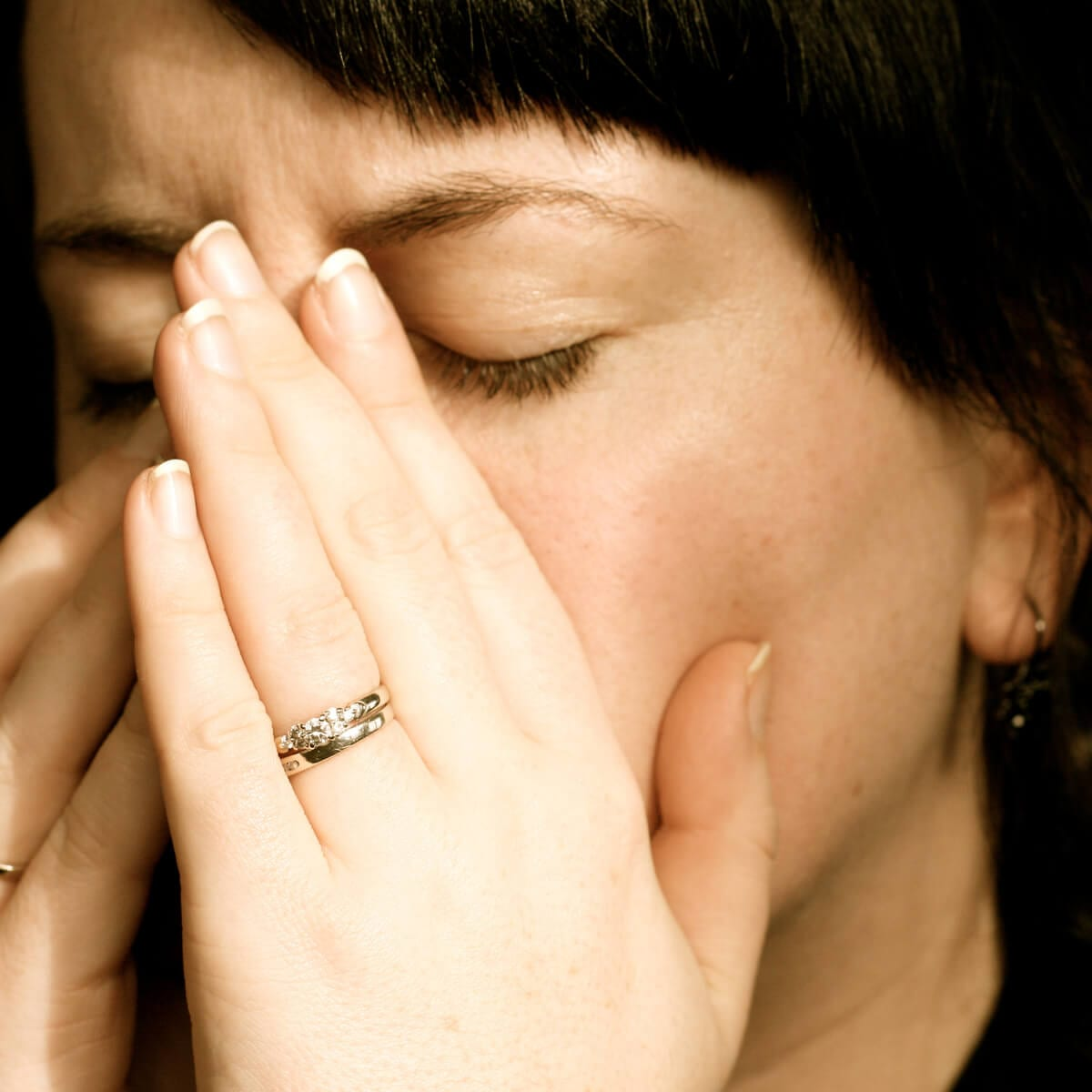 woman covering her hands to cough