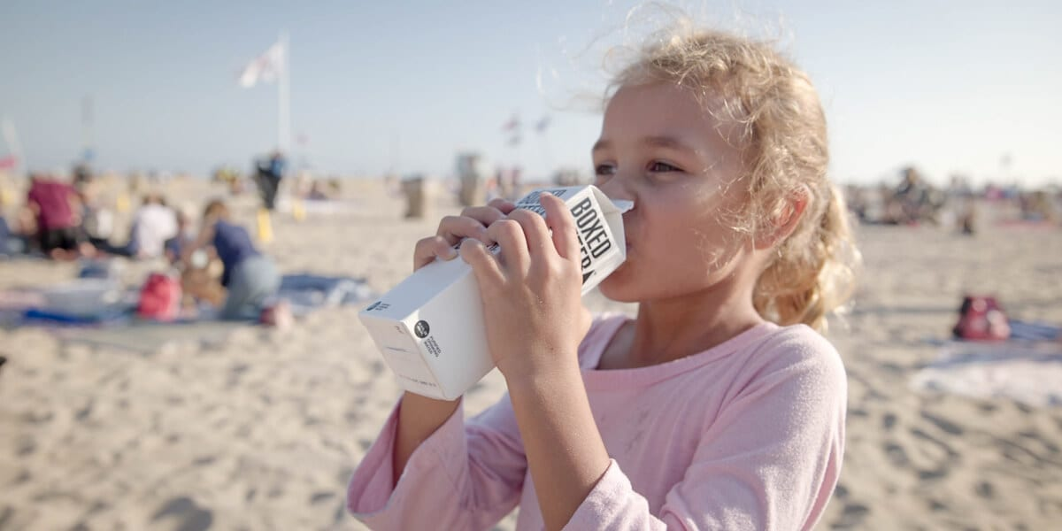 blond girl drinking boxed water on the beach