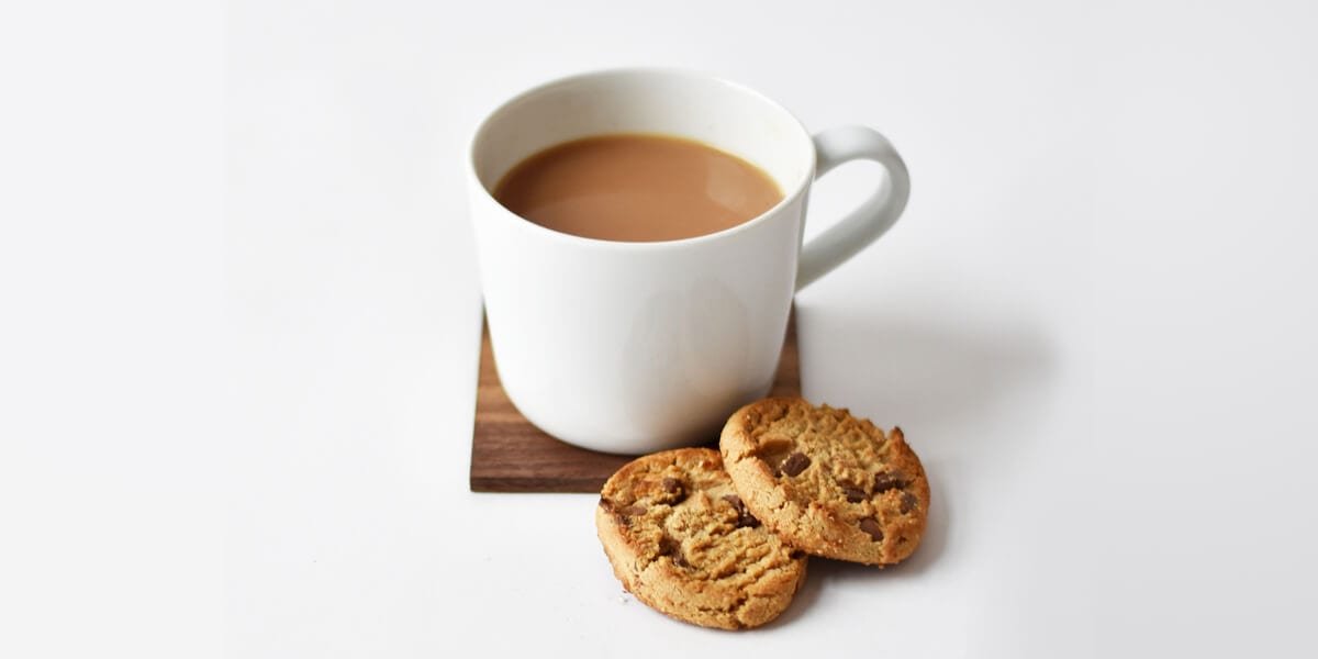mug of coffee on coaster, chocolate chip cookies