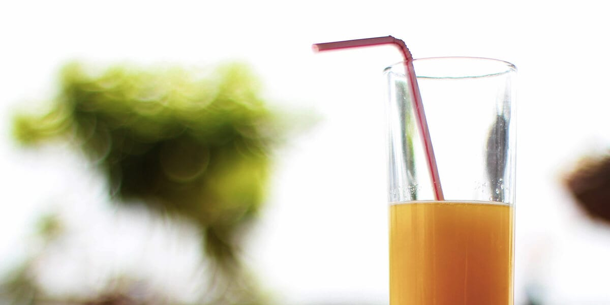 glass of orange juice with plastic straw