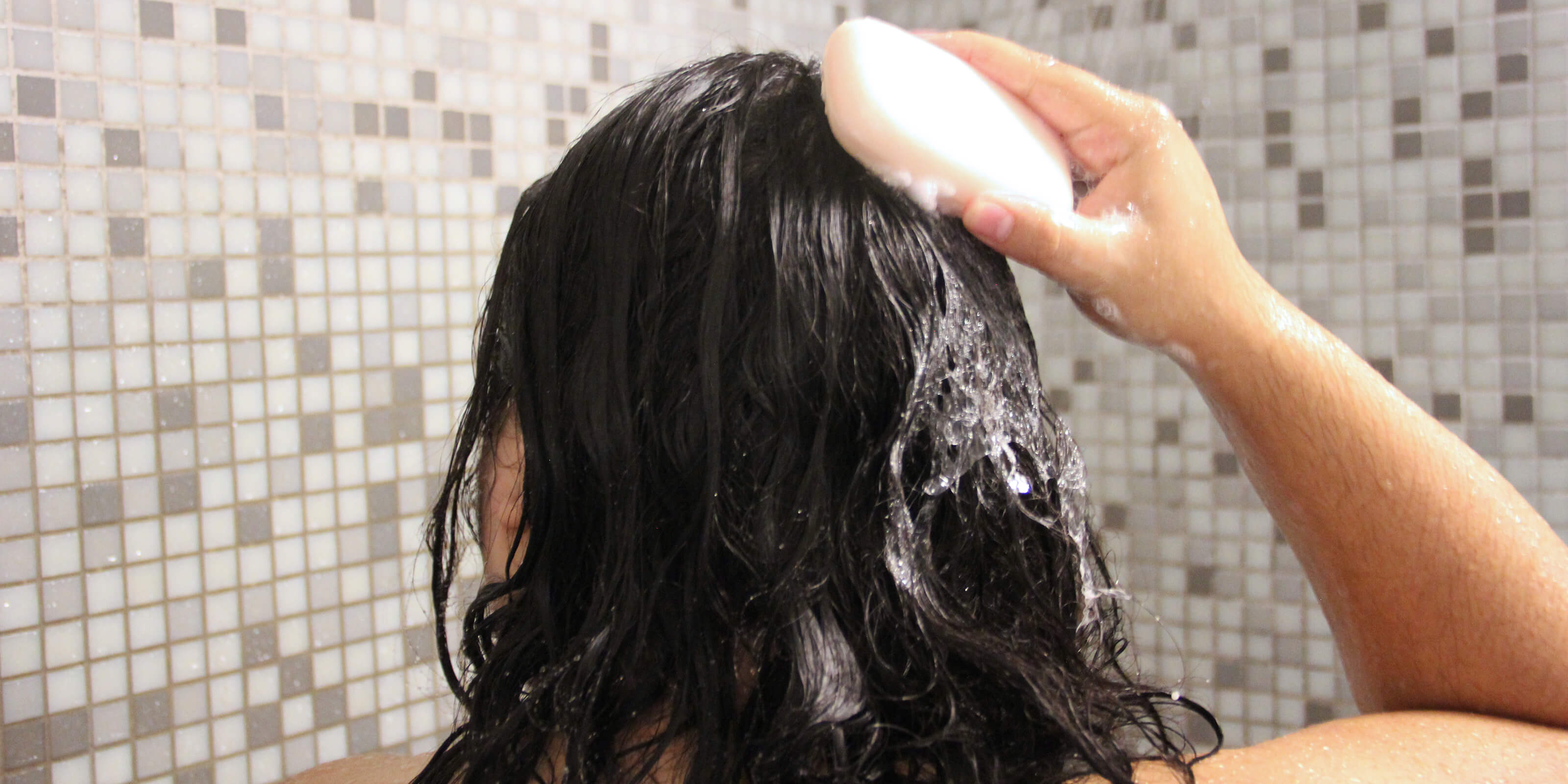 woman rubbing shampoo bar on hair