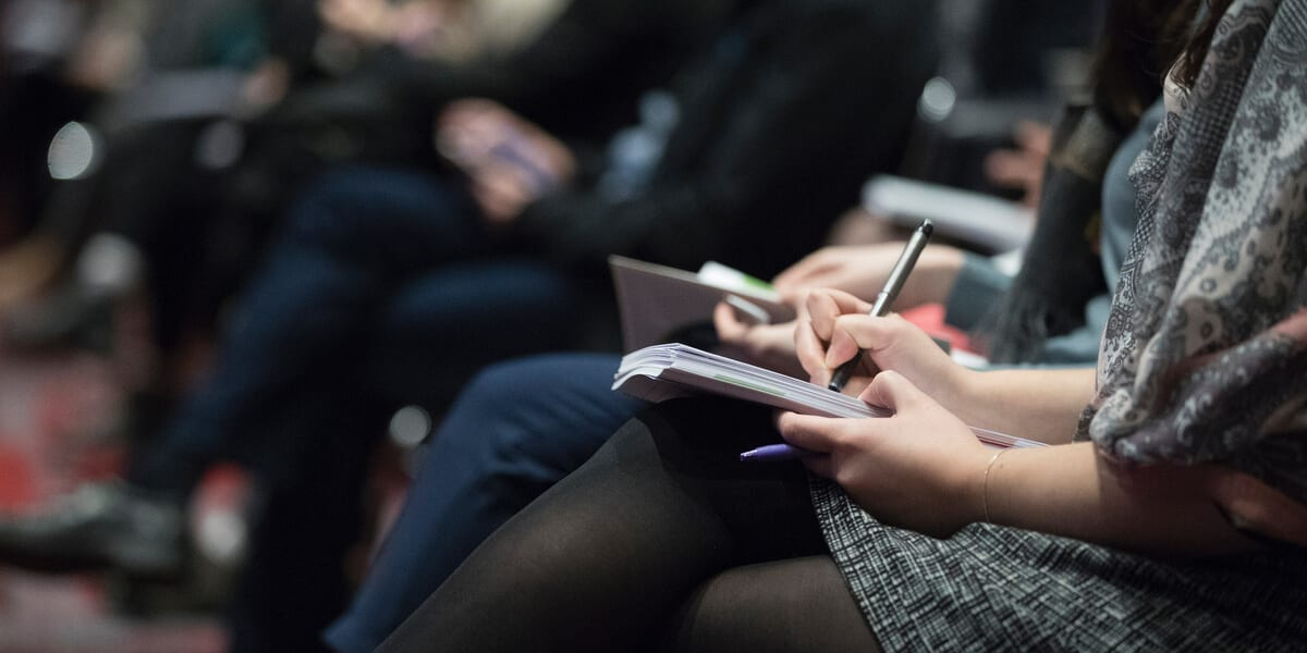 woman taking notes in conference