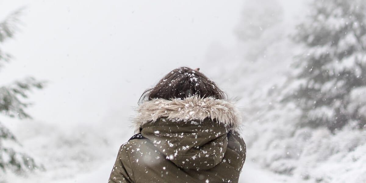 woman walking in snow wearing winter coat