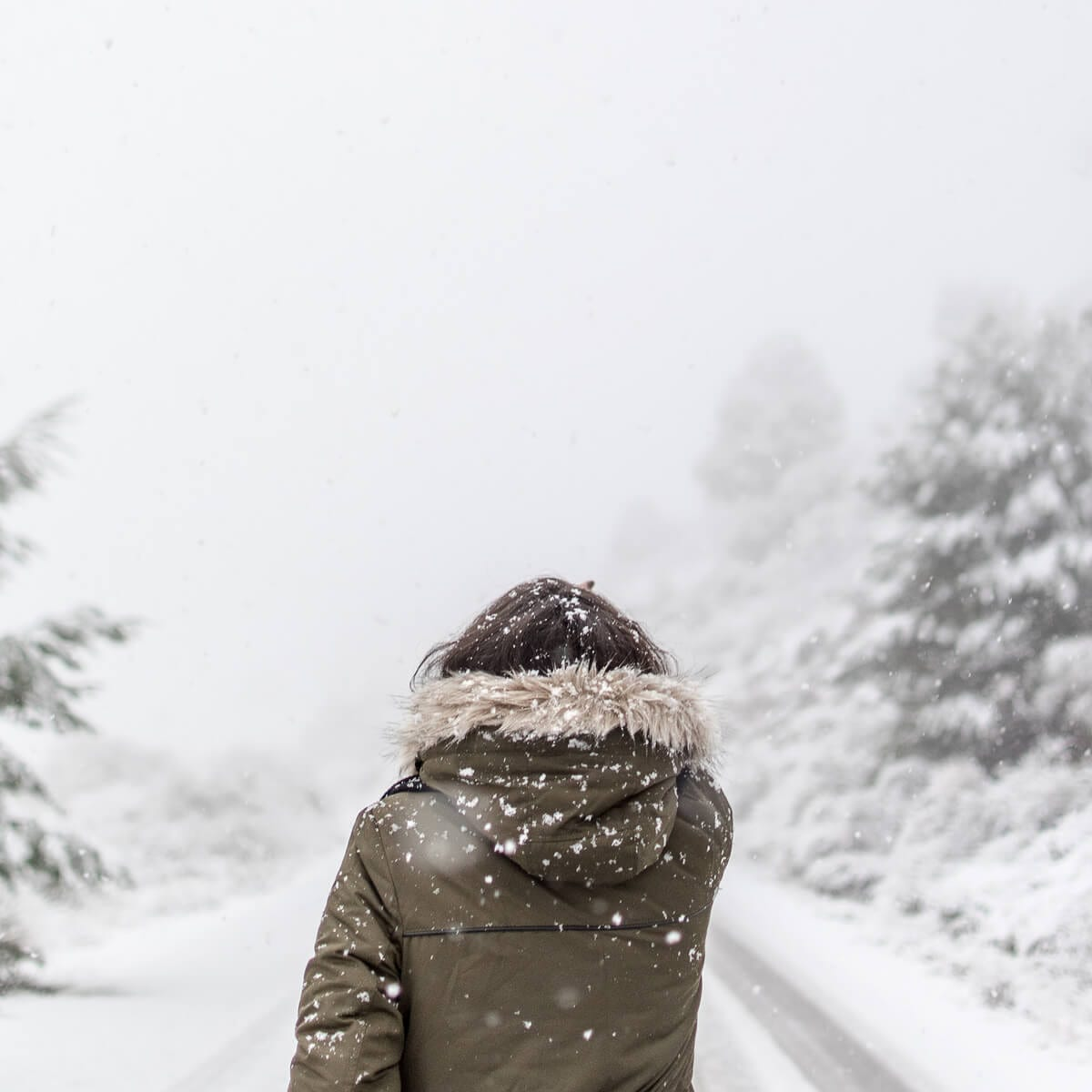 woman walking in snow wearing winter coat