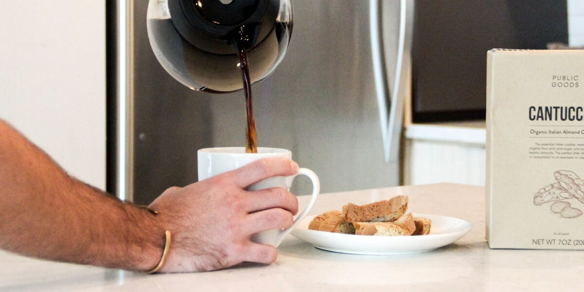 man pouring coffee from pot into mug, public goods cantuccini