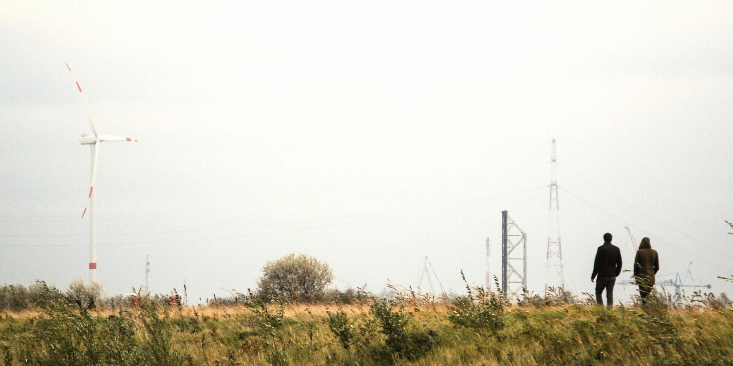 couple walking in field with wind turbines