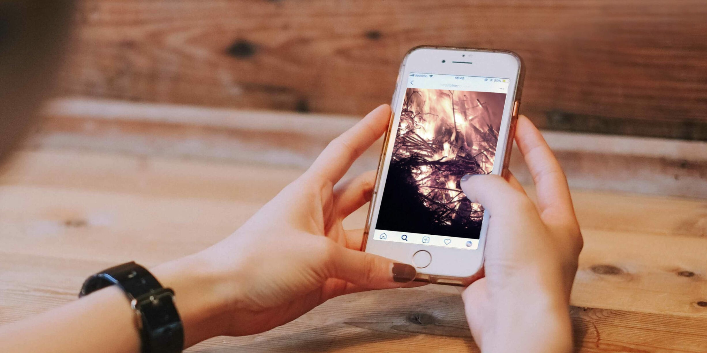 Woman looking at photo of fire on white iPhone