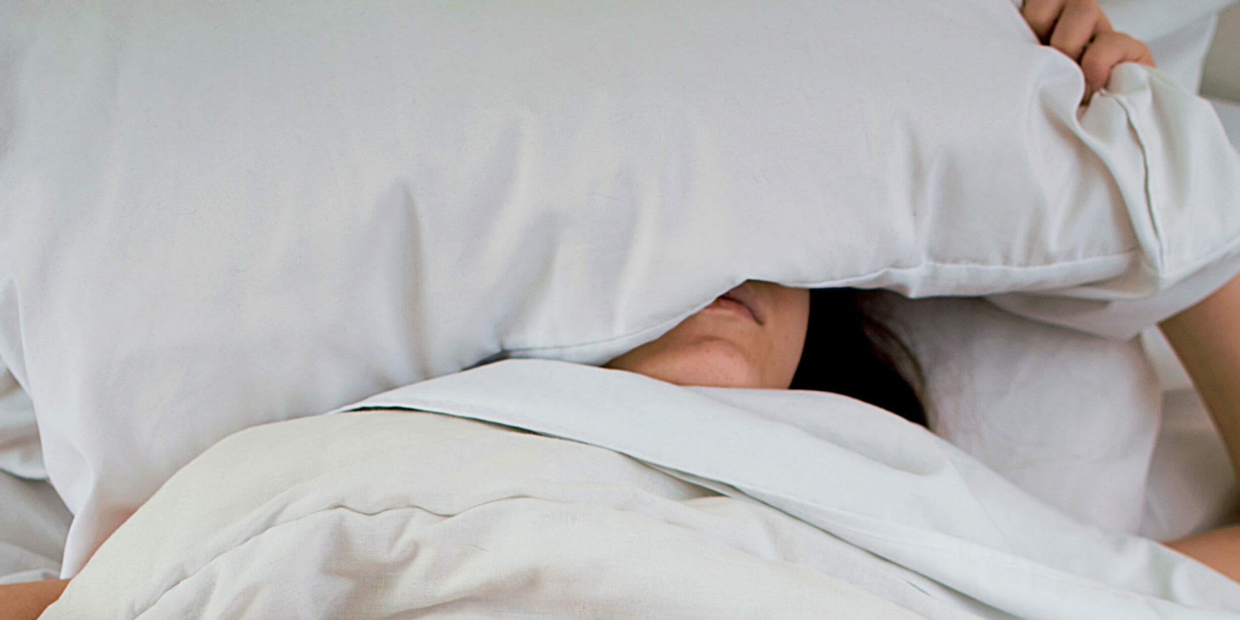 woman sleeping, pillow on head