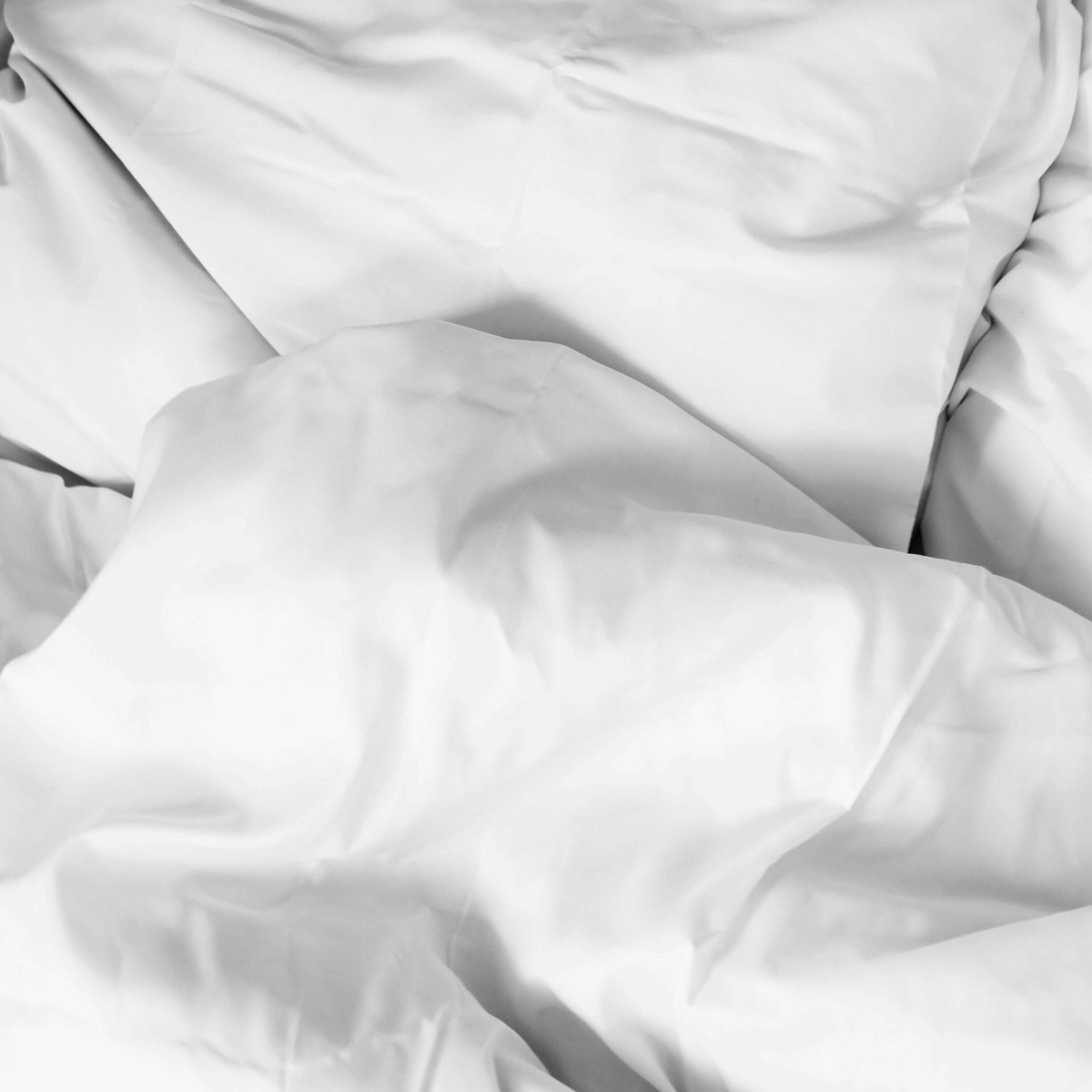 two white pillows, white comforter