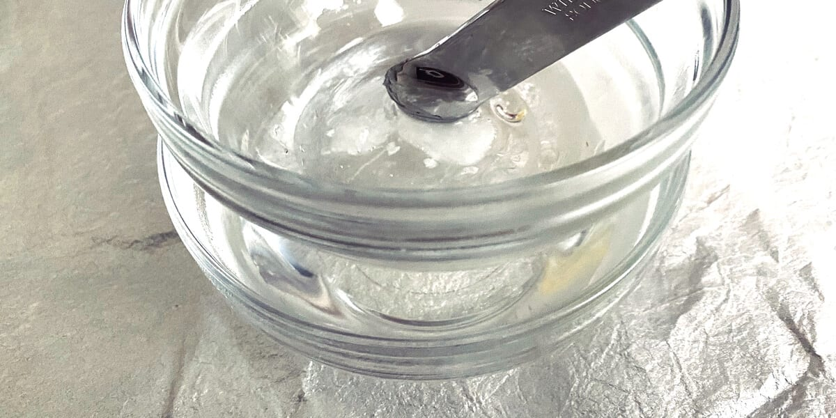 measuring spoon scooping out coconut oil from bowl