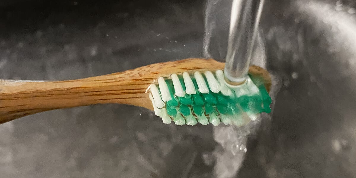 rinse toothbrush bristles in sink