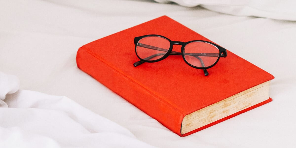 red hardcover book with reading glasses