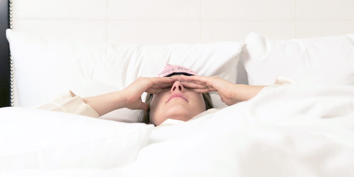 woman laying in bed and rubbing eyes