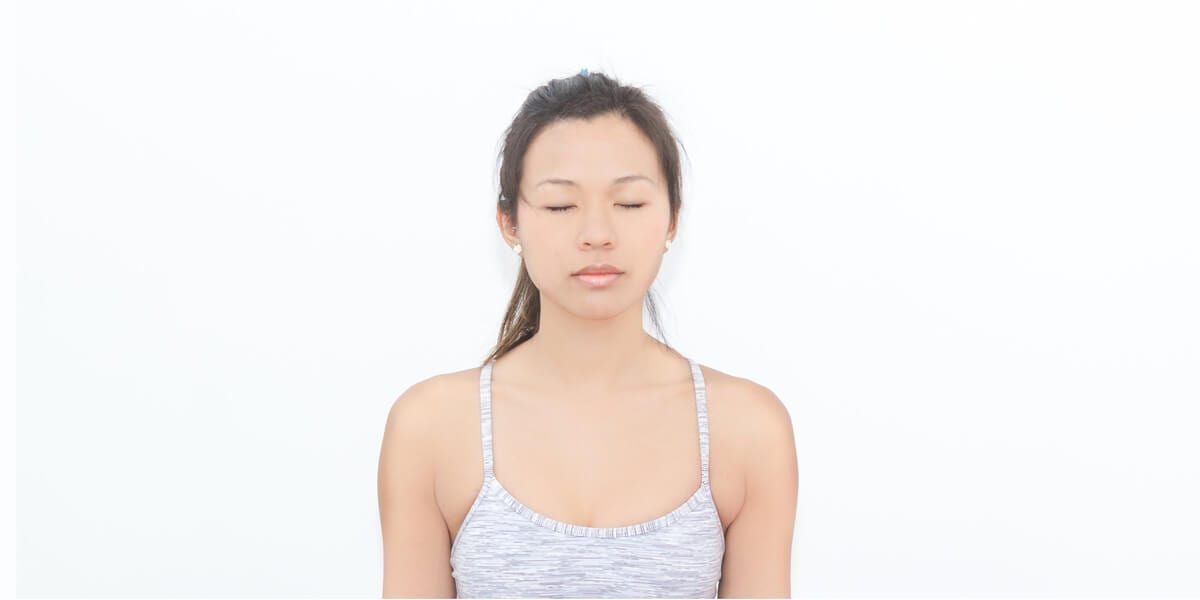 woman in gray tanktop practicing meditation