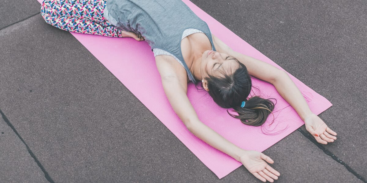 woman stretching on pink yoga mat