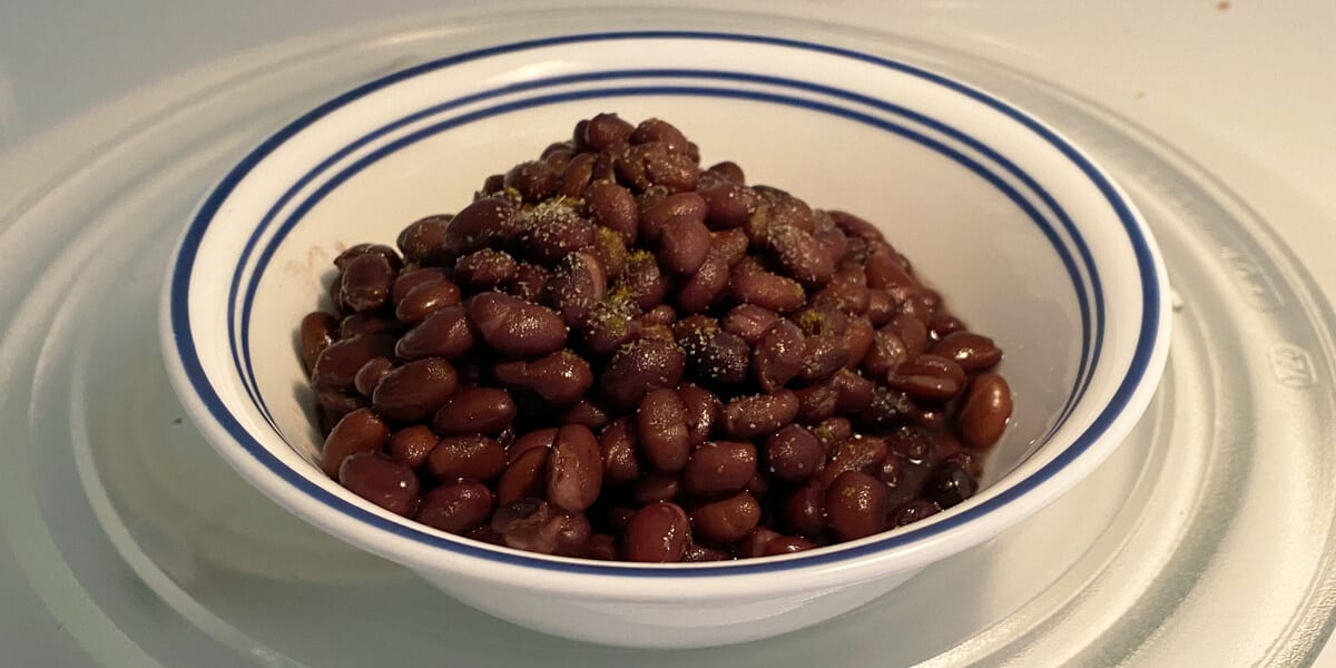 bowl of black beans in the microwave