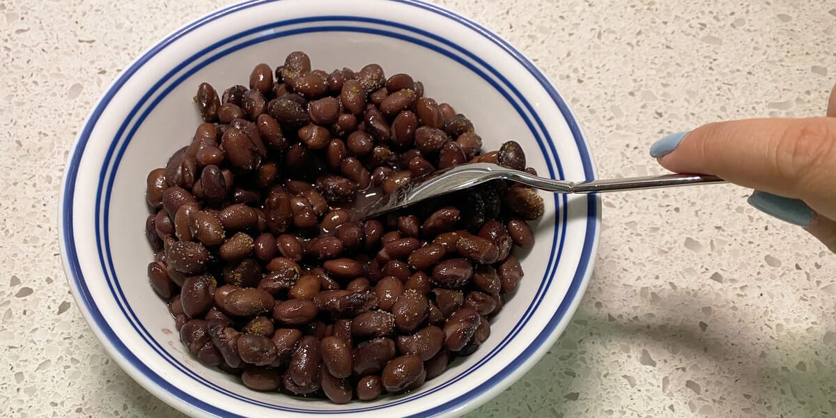 mixing bowl of black beans with spoon