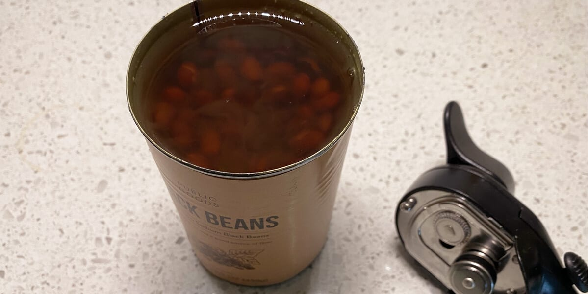 open can of black beans next to can opener