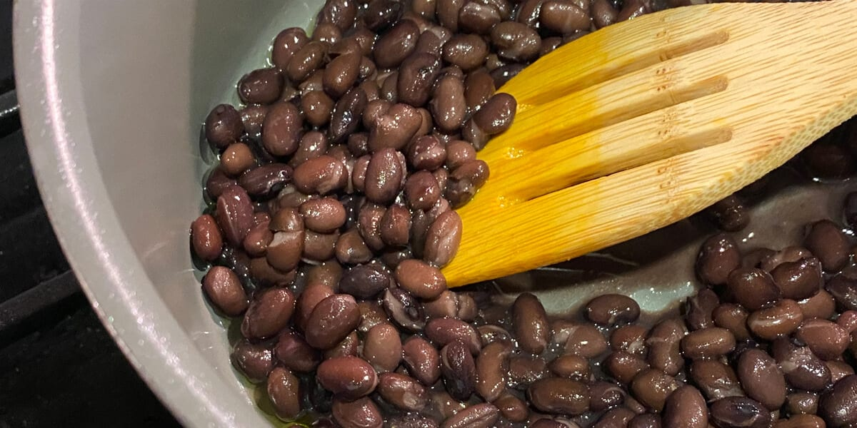 mixing black beans with wooden slotted spatula