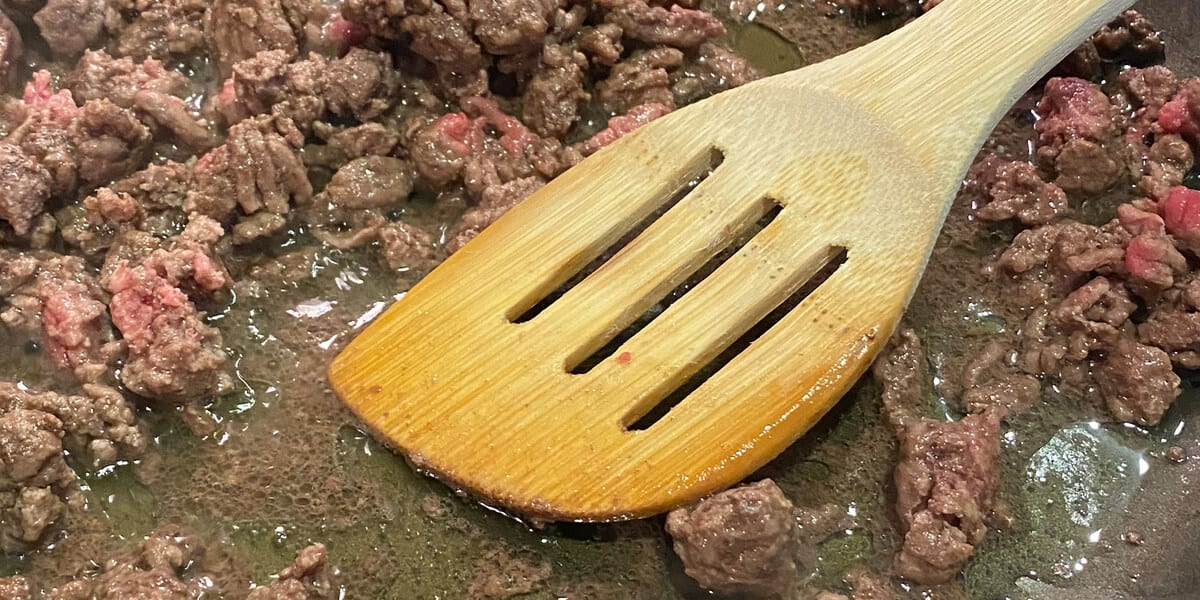 stirring beef with a slotted spoon