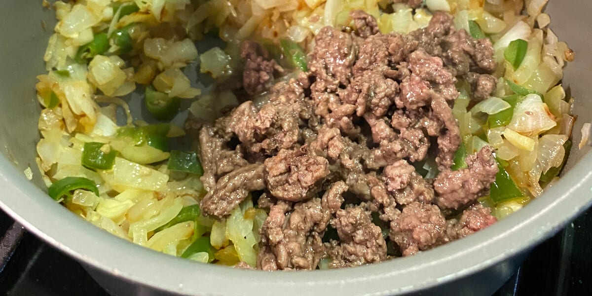beef in a pot with garlic, onions and peppers