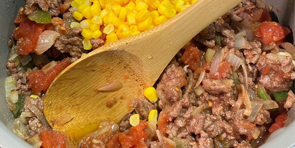 corn and tomatoes in a pot with beef, onions, garlic and peppers