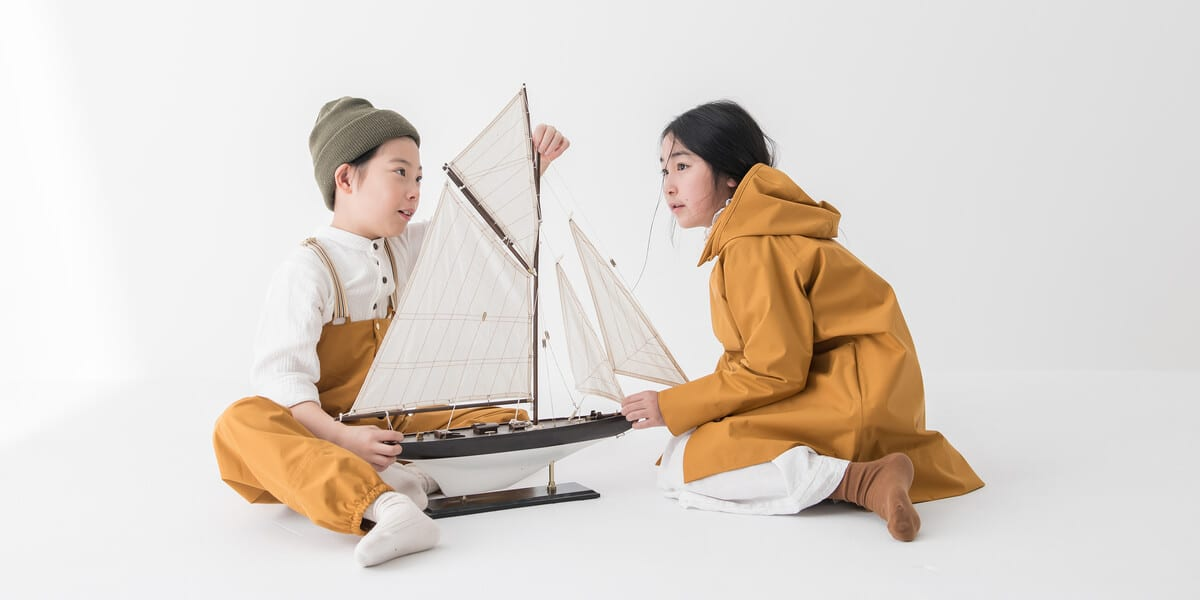 two children in waterproof clothes playing with a model ship